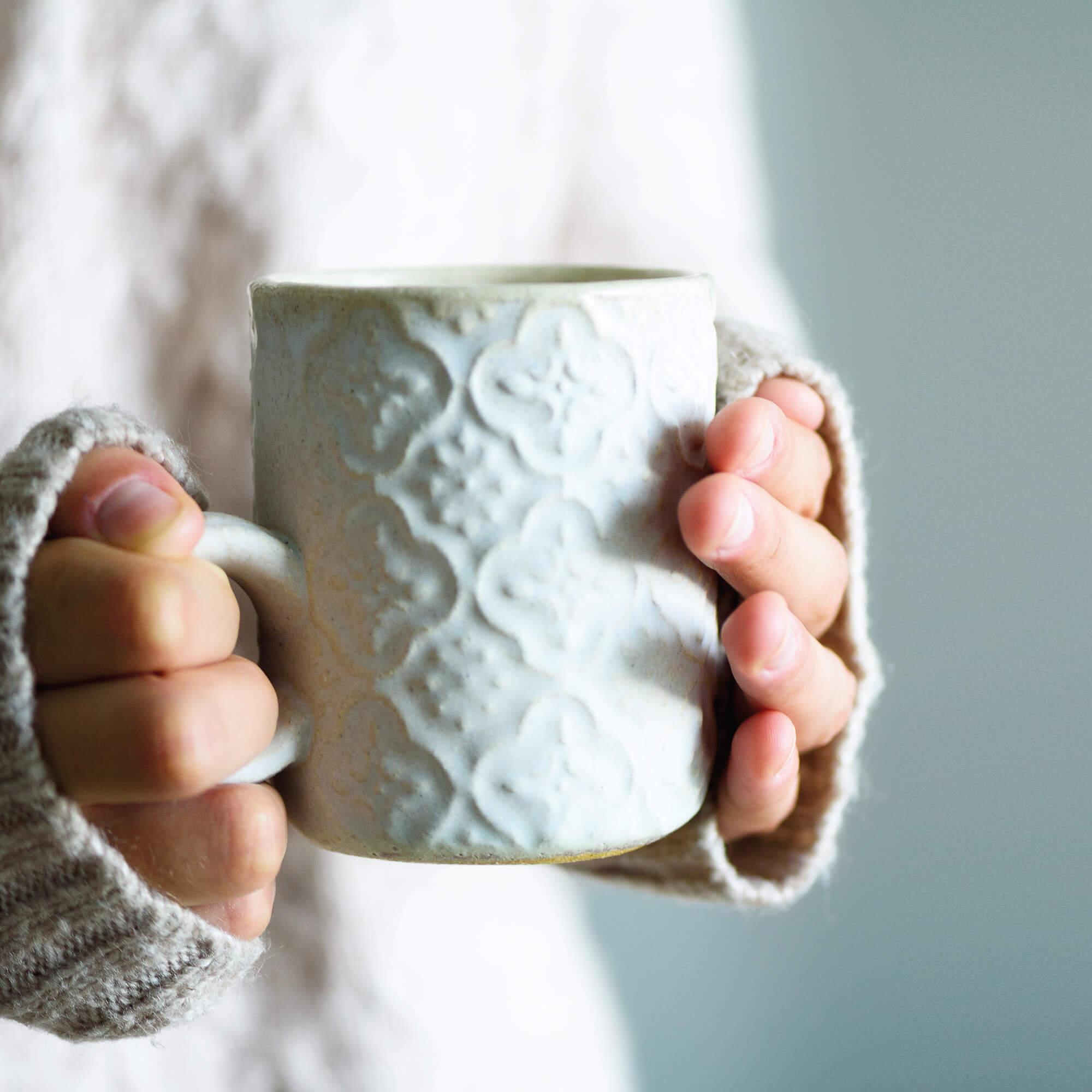 A girls hands holding a mug