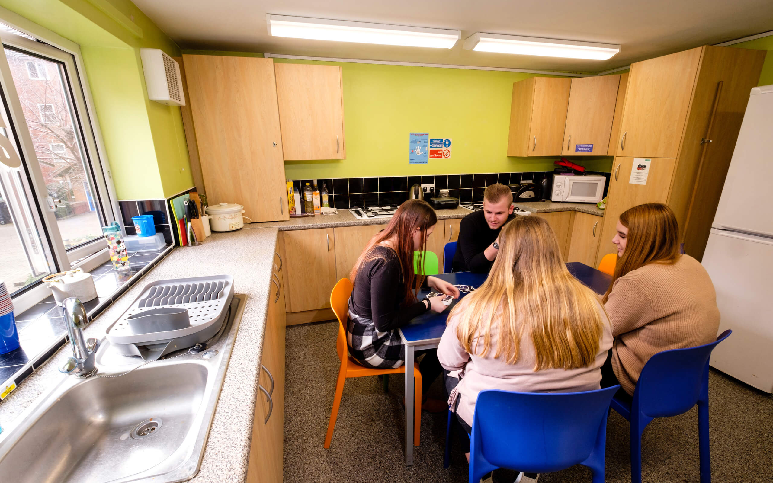 Four students socialising in halls kitchen