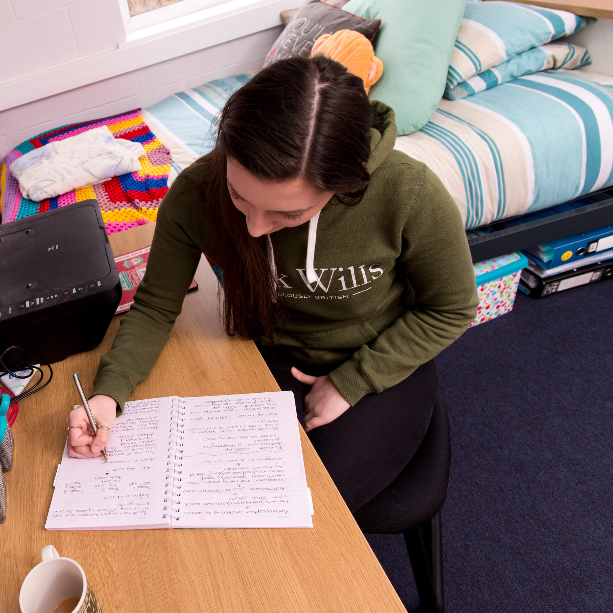 Student writing in notebook at a bedroom desk in halls