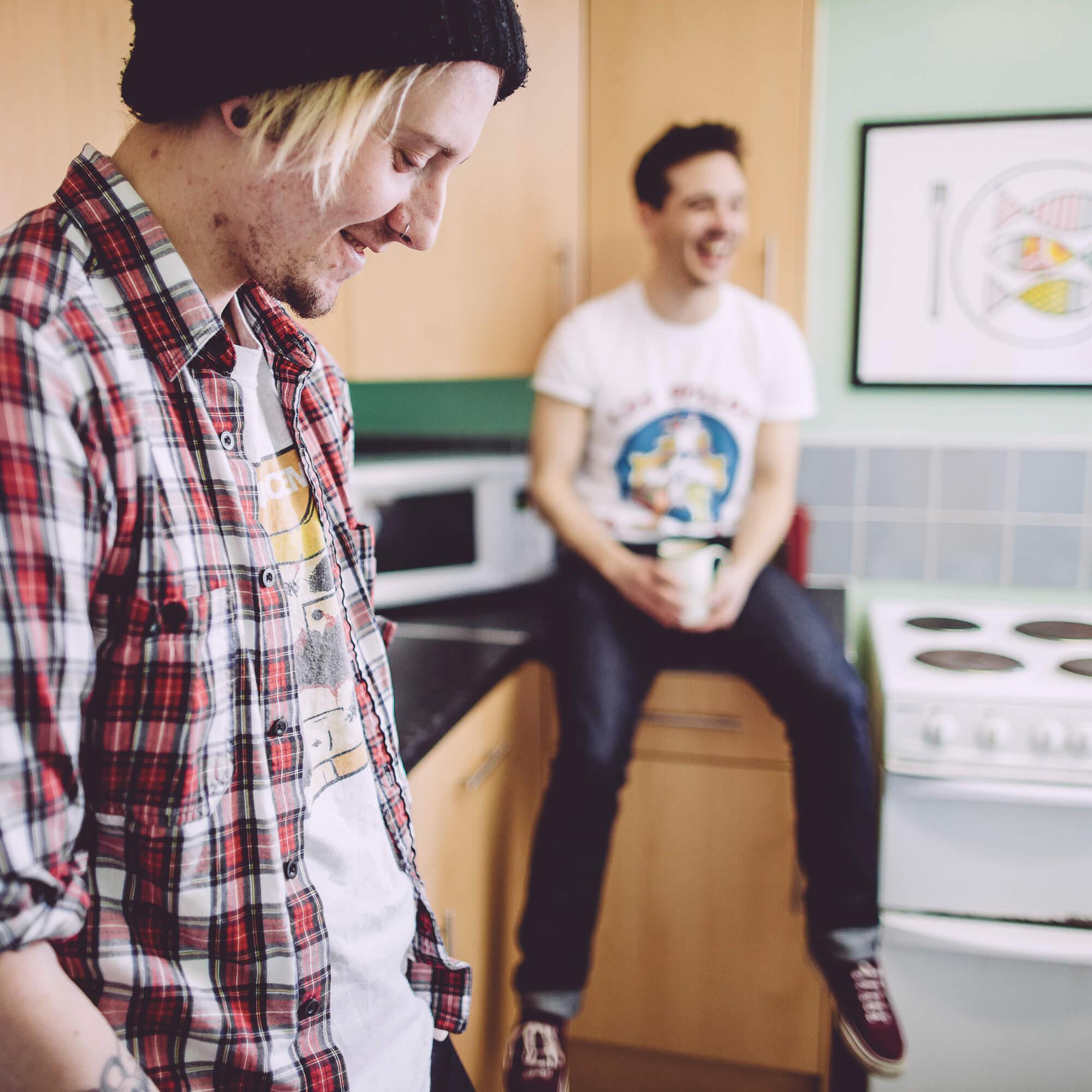 Two boys in halls kitchen, one sitting on worktop