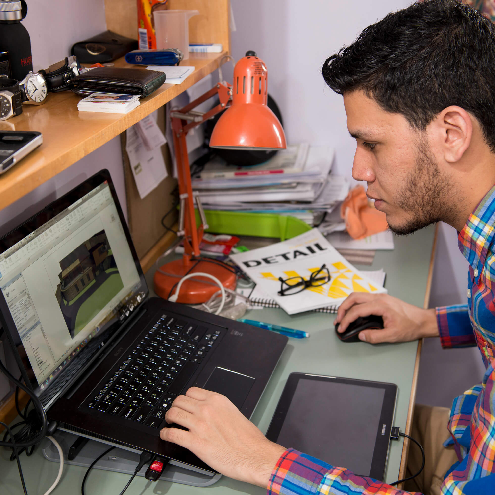 Student working on laptop at desk in halls