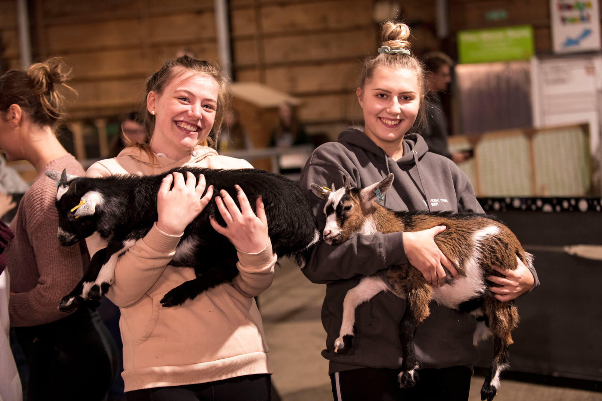 Two students holding two goats