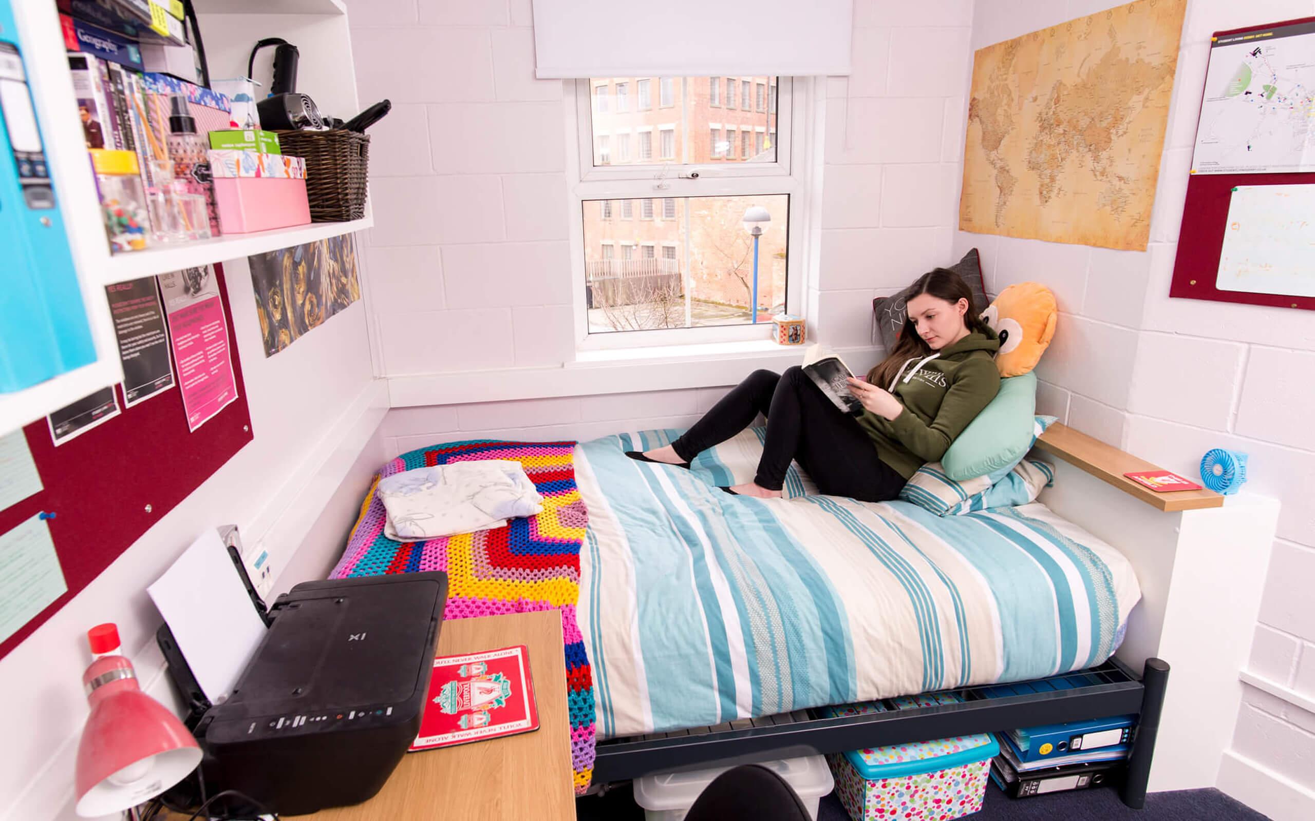 Person sitting on their bed in their Peak Court En Suite Premium Bedroom