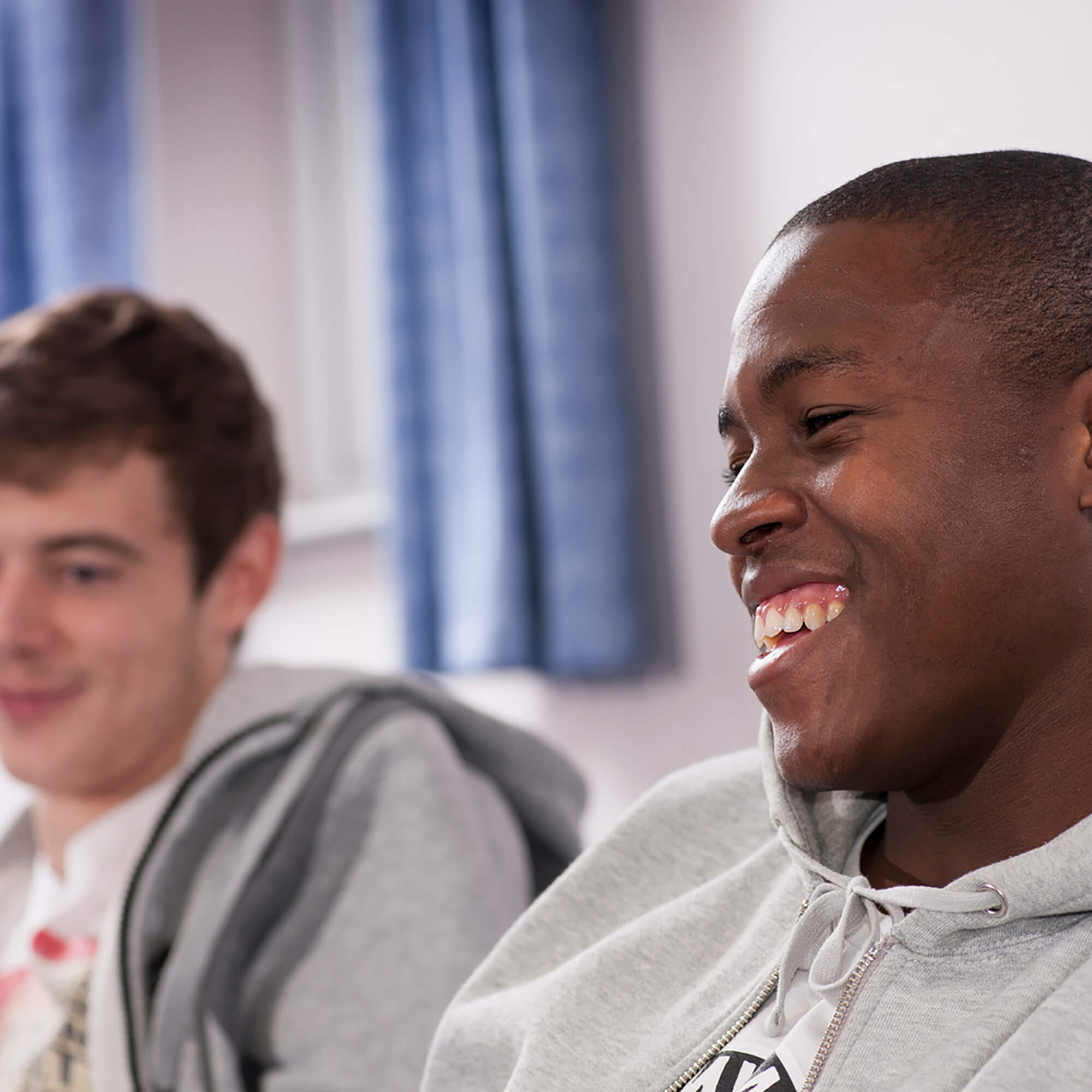Two students sitting and smiling