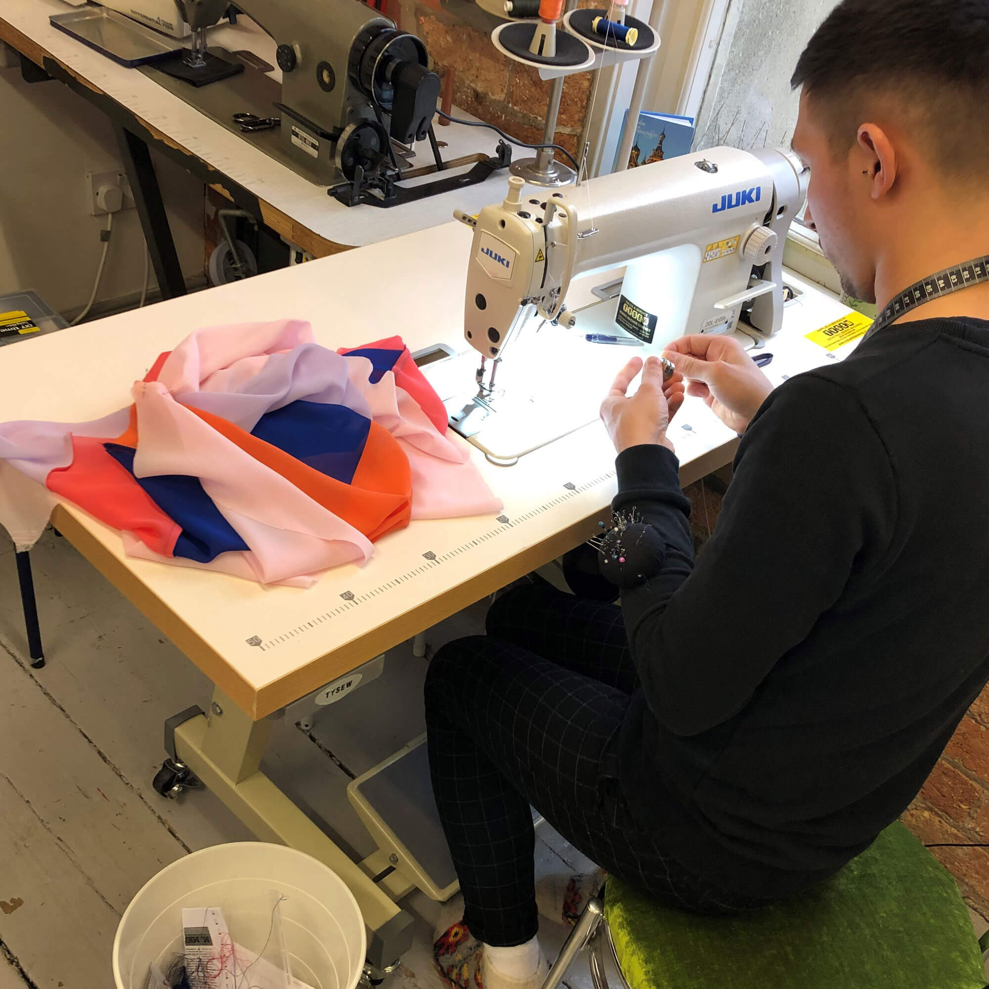 A man in a dark jumper sat with his back to the camera on his sewing machine