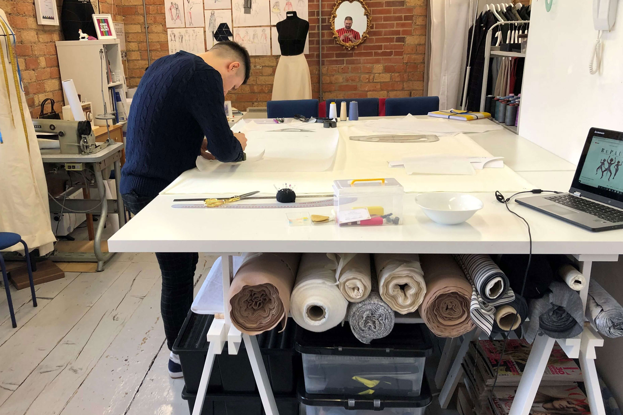A man in a navy jumper sketching in his studio