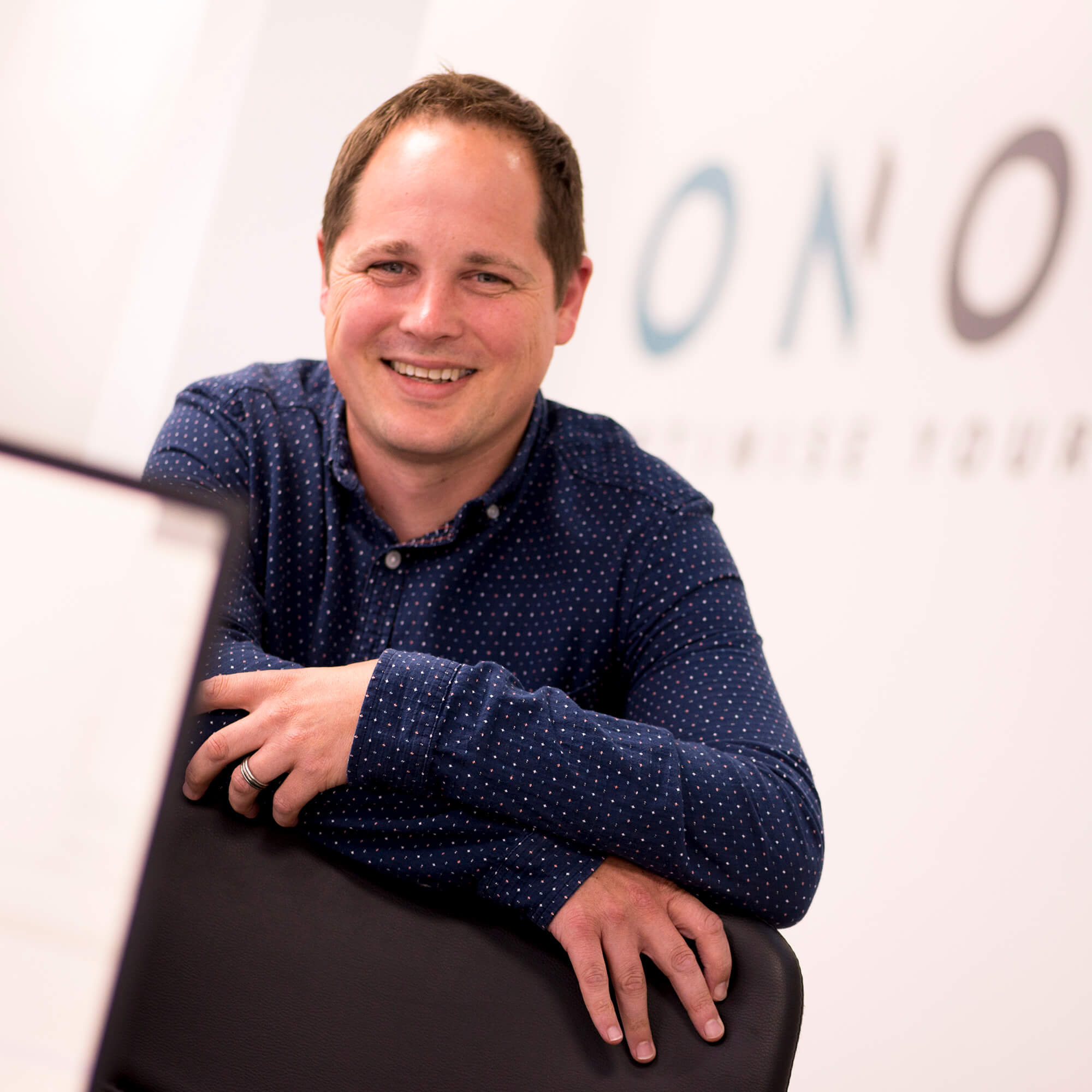 The Manager of Onomi smiles at the camera with his brand name in the background on the wall