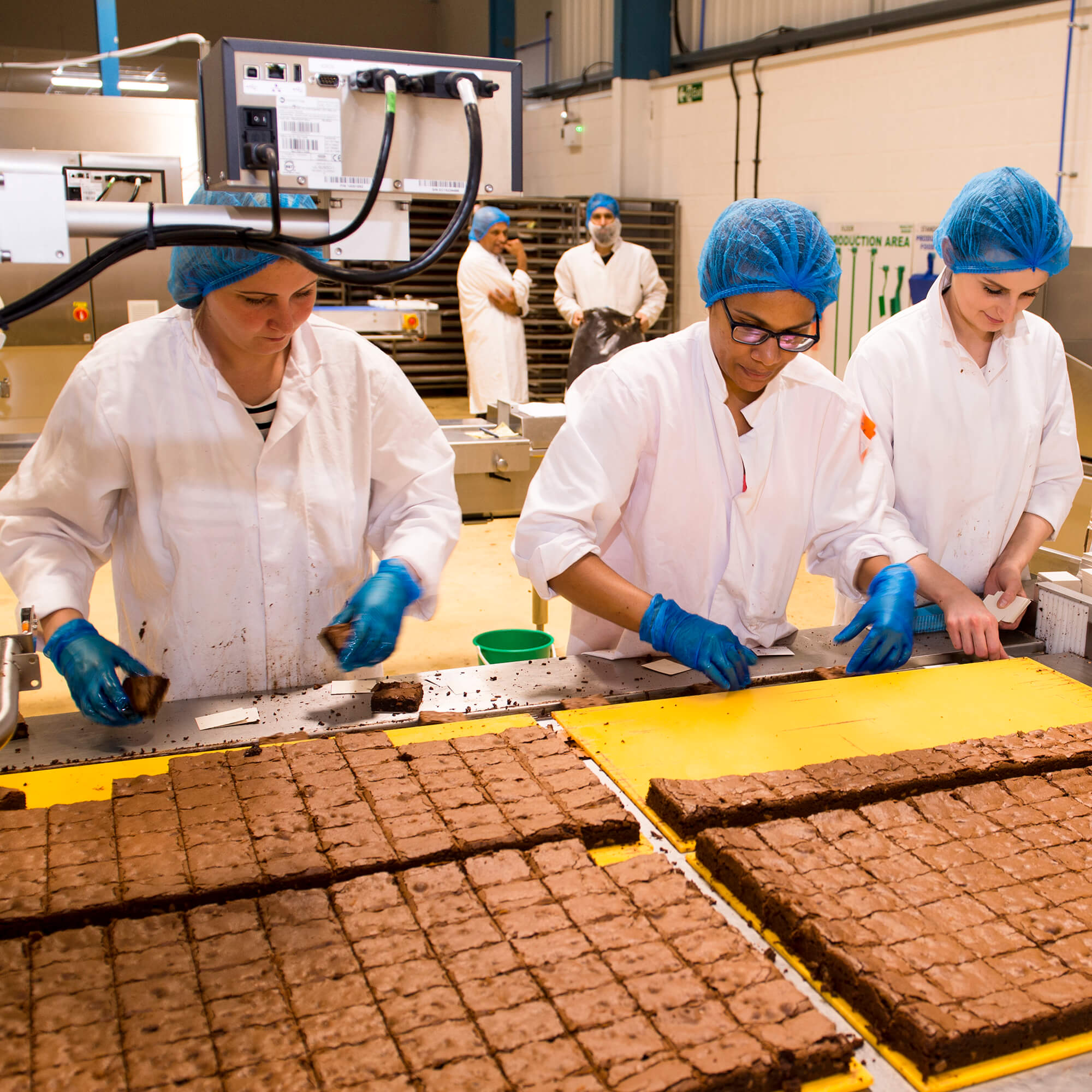 Three women with white overalls and blue hair nets handle industrial amounts of brownie in a factory