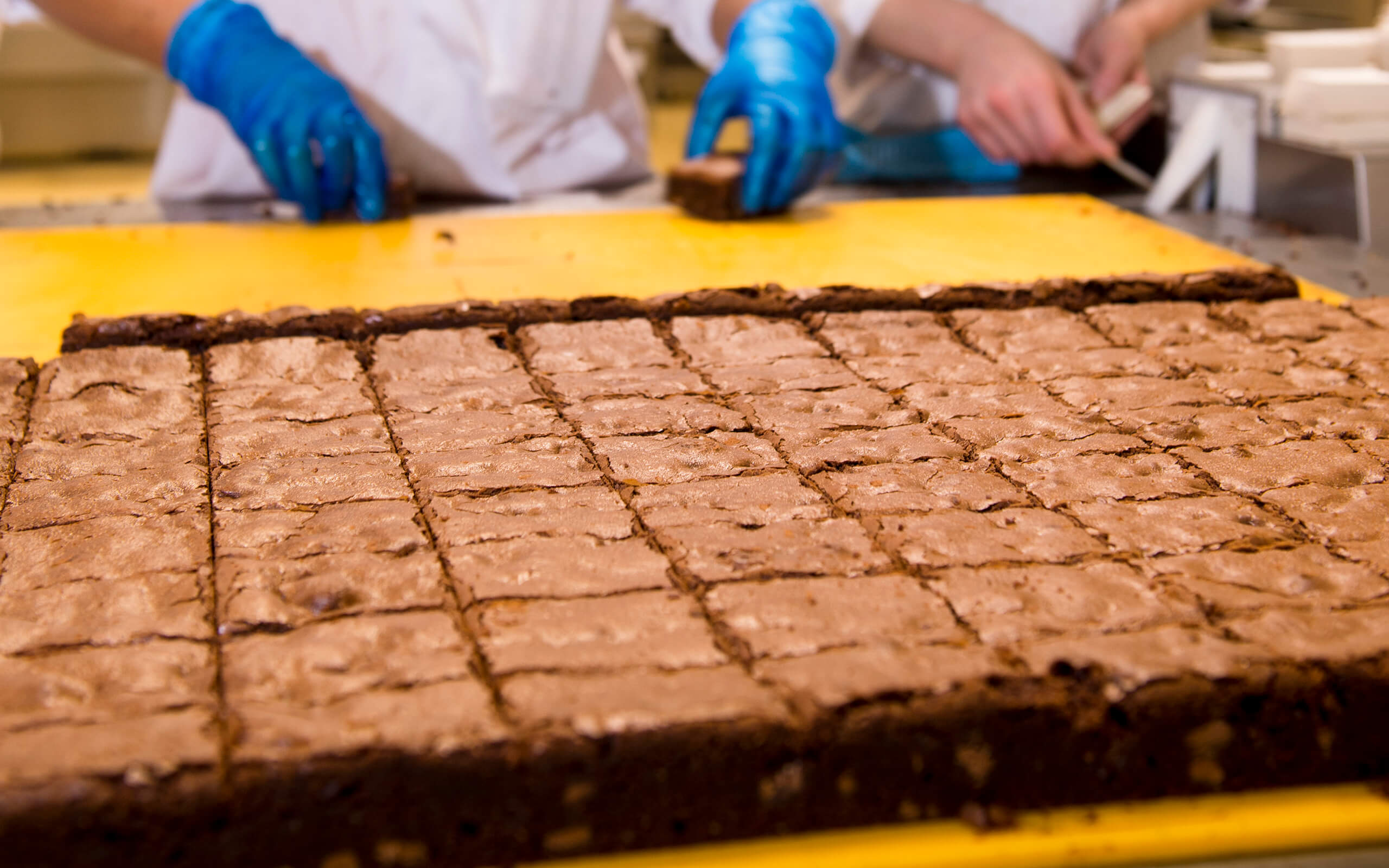 Industrial amounts of brownie being handled on a yellow board with factory worker's hands in the background