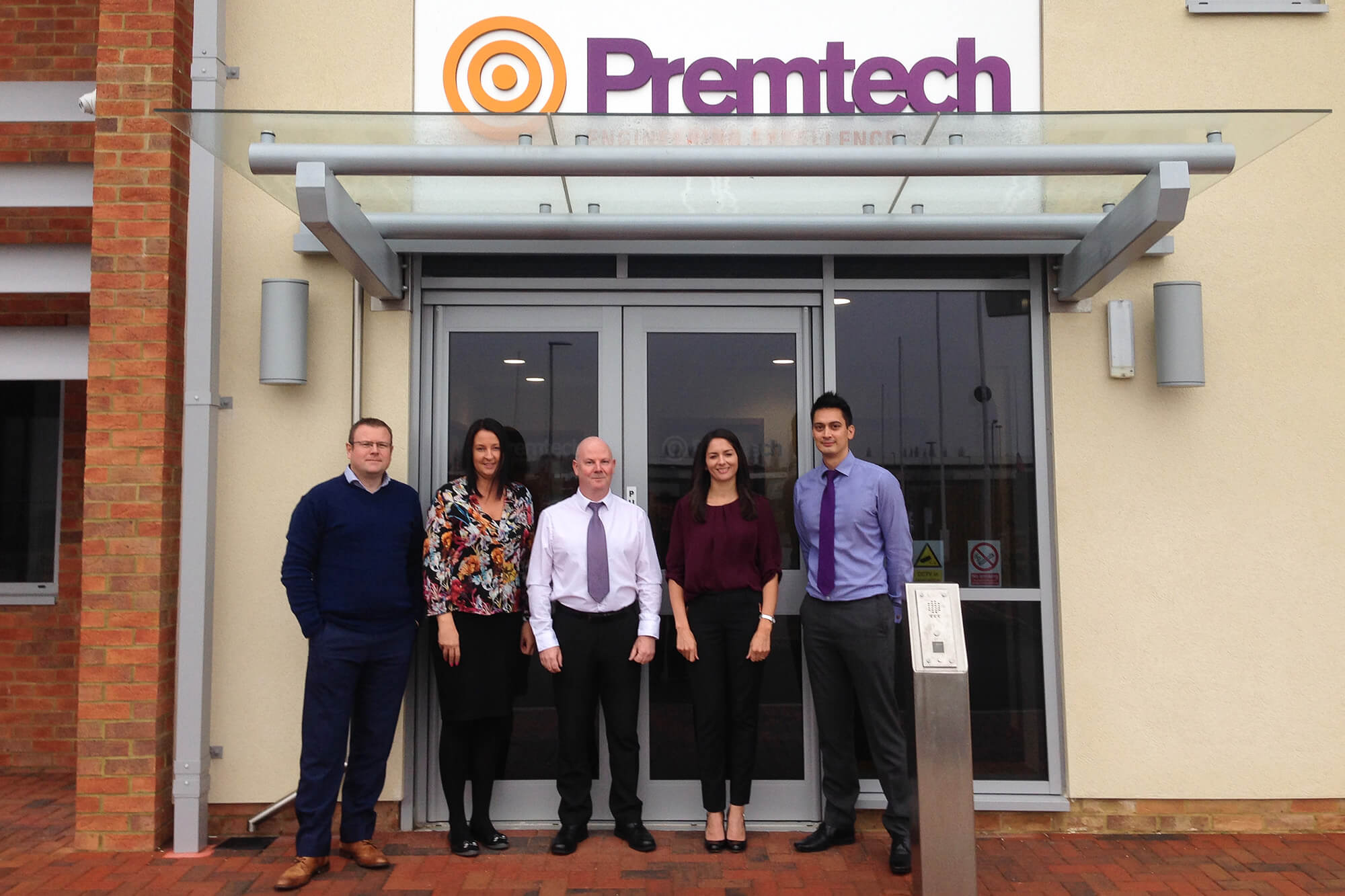 Premtech staff stand outside their office building