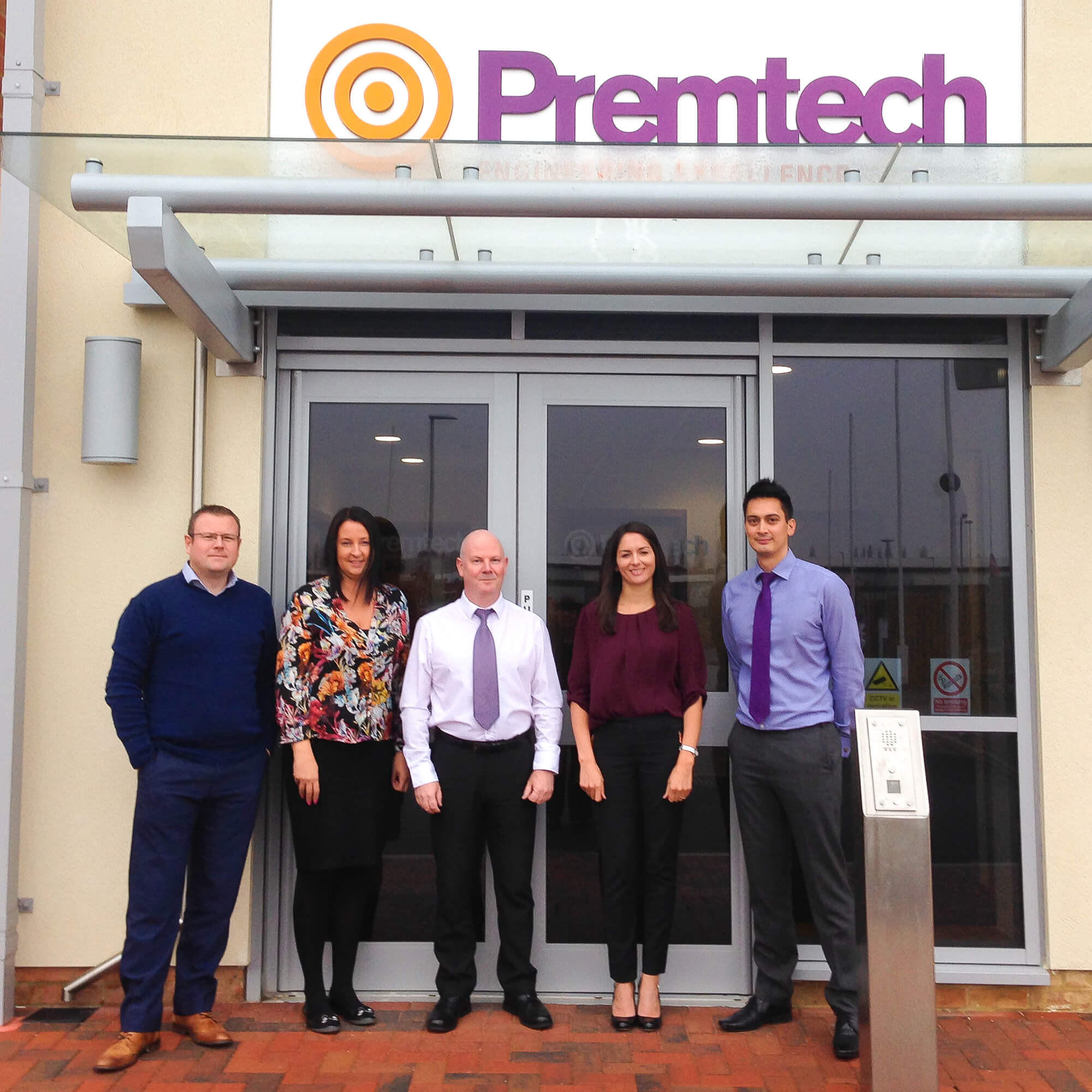The Premtech team stand outside their office below the Premtech sign