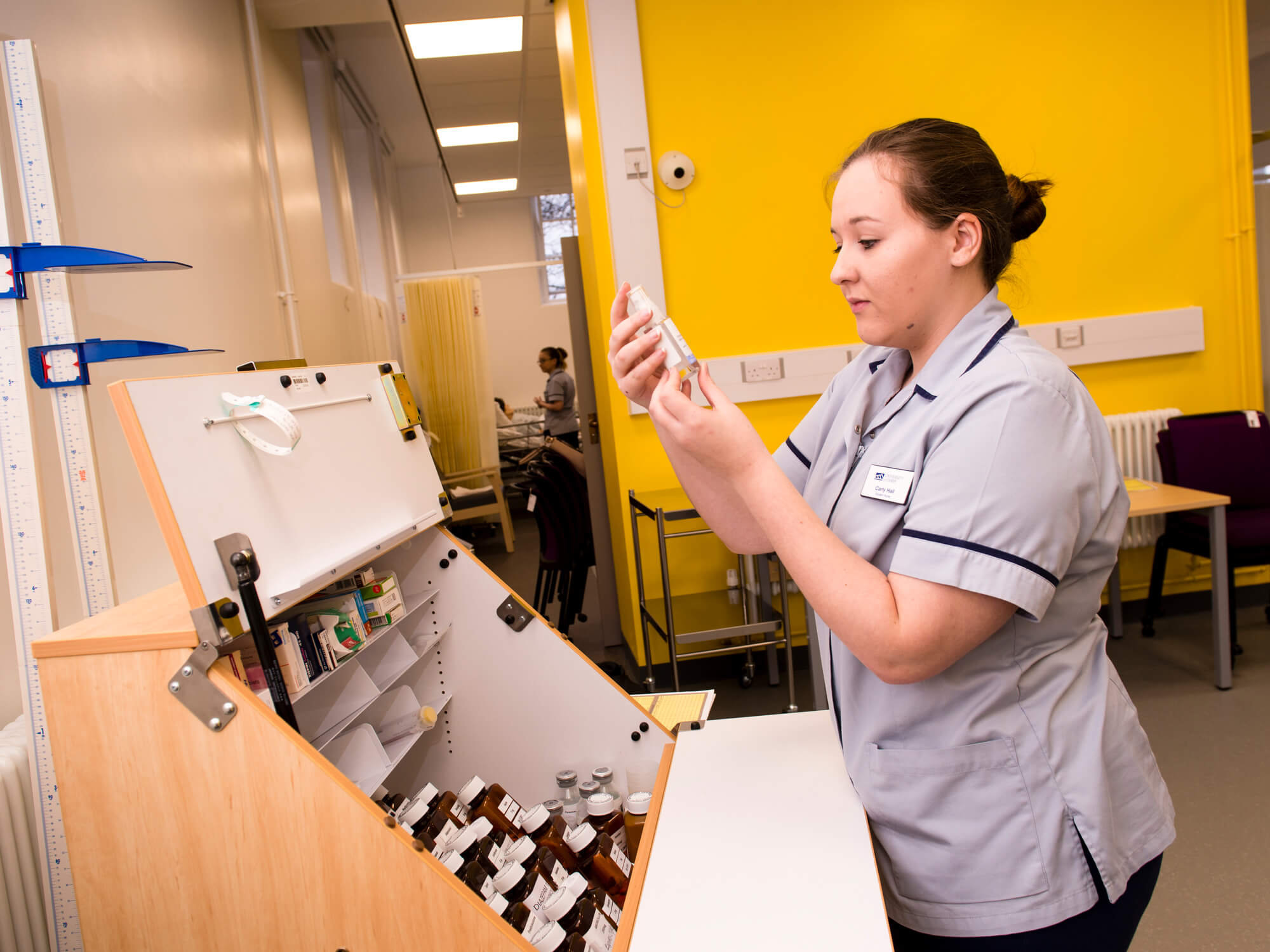 A nurse looks at a bottle of medicine from a cabinet in front of a bright yellow wall.