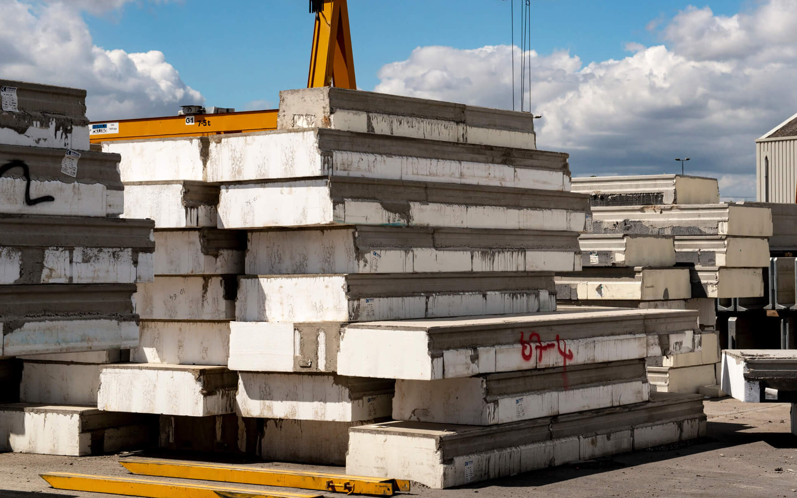 A pile of concrete in a builders yard, with a bright blue sky