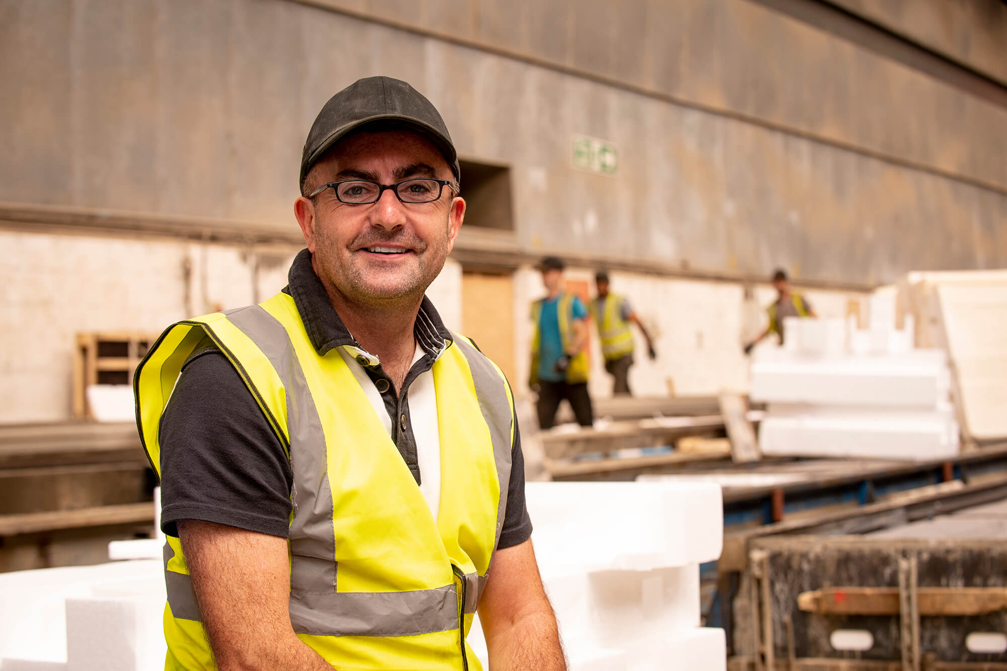 A man in a high viz smiles at the camera in an indoor construction site