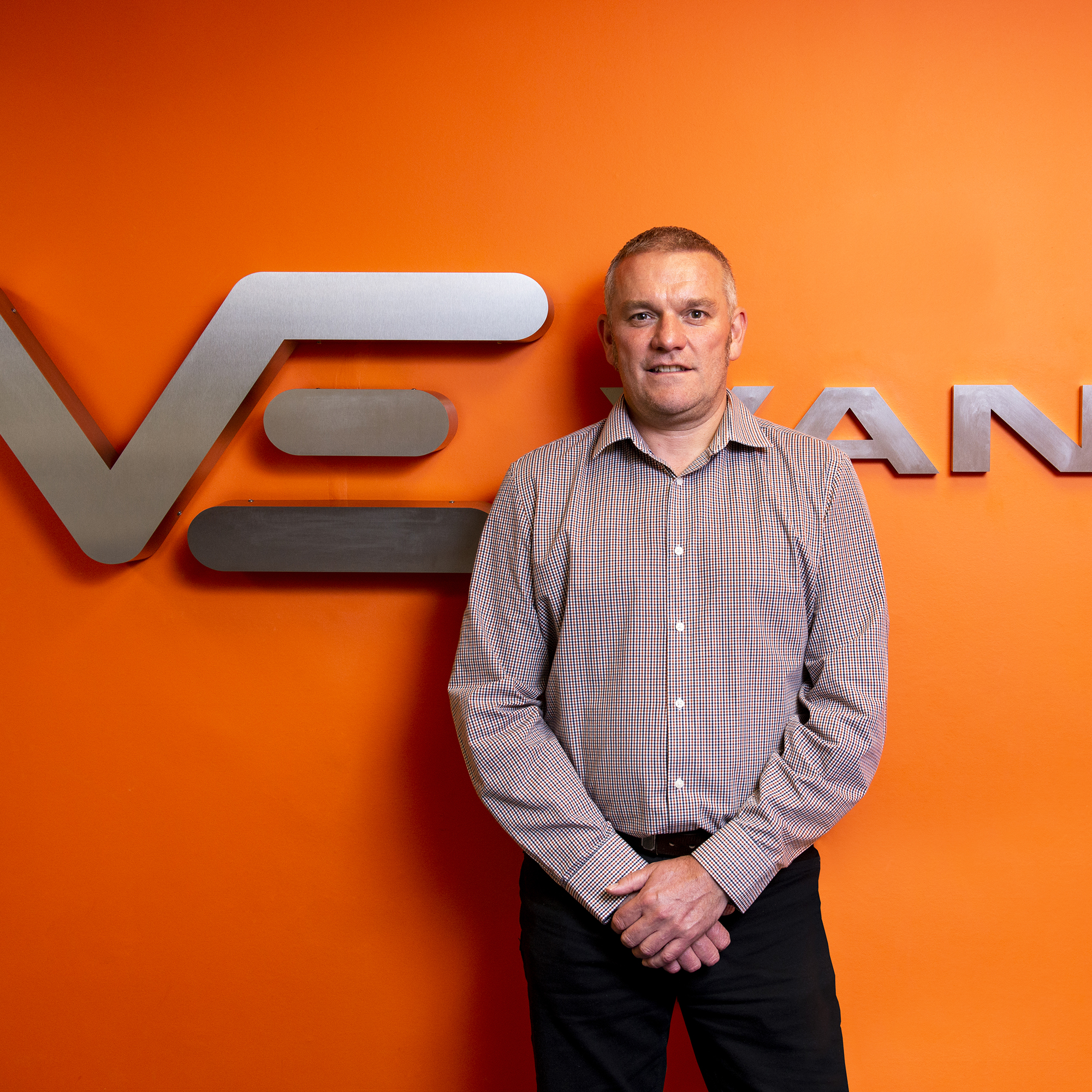 Van Elle Manager stands in front of his orange sign