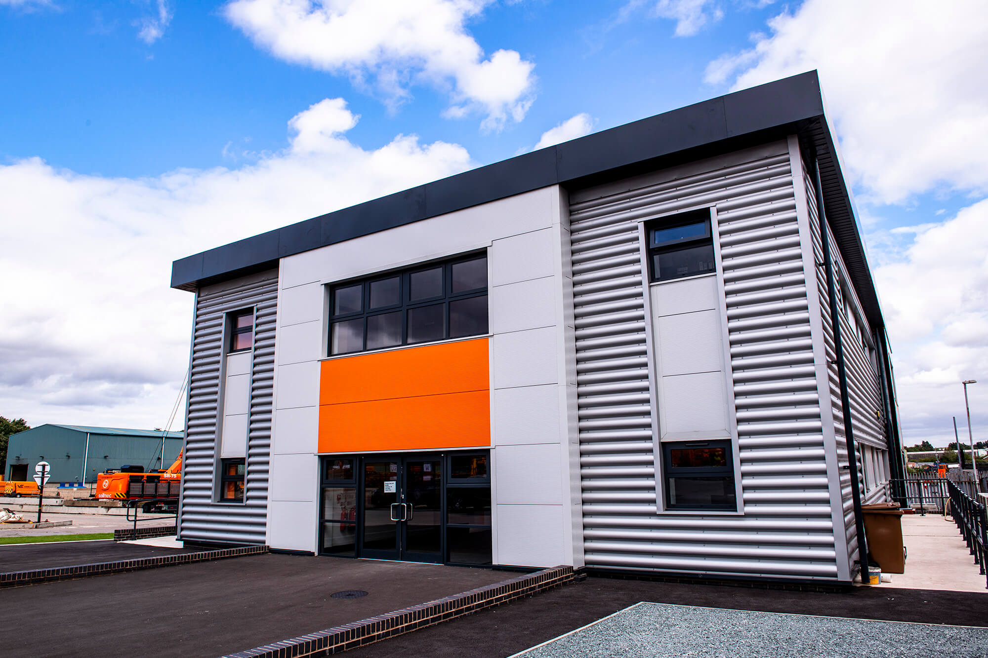 A grey building with an orange panel against a blue sky with white clouds