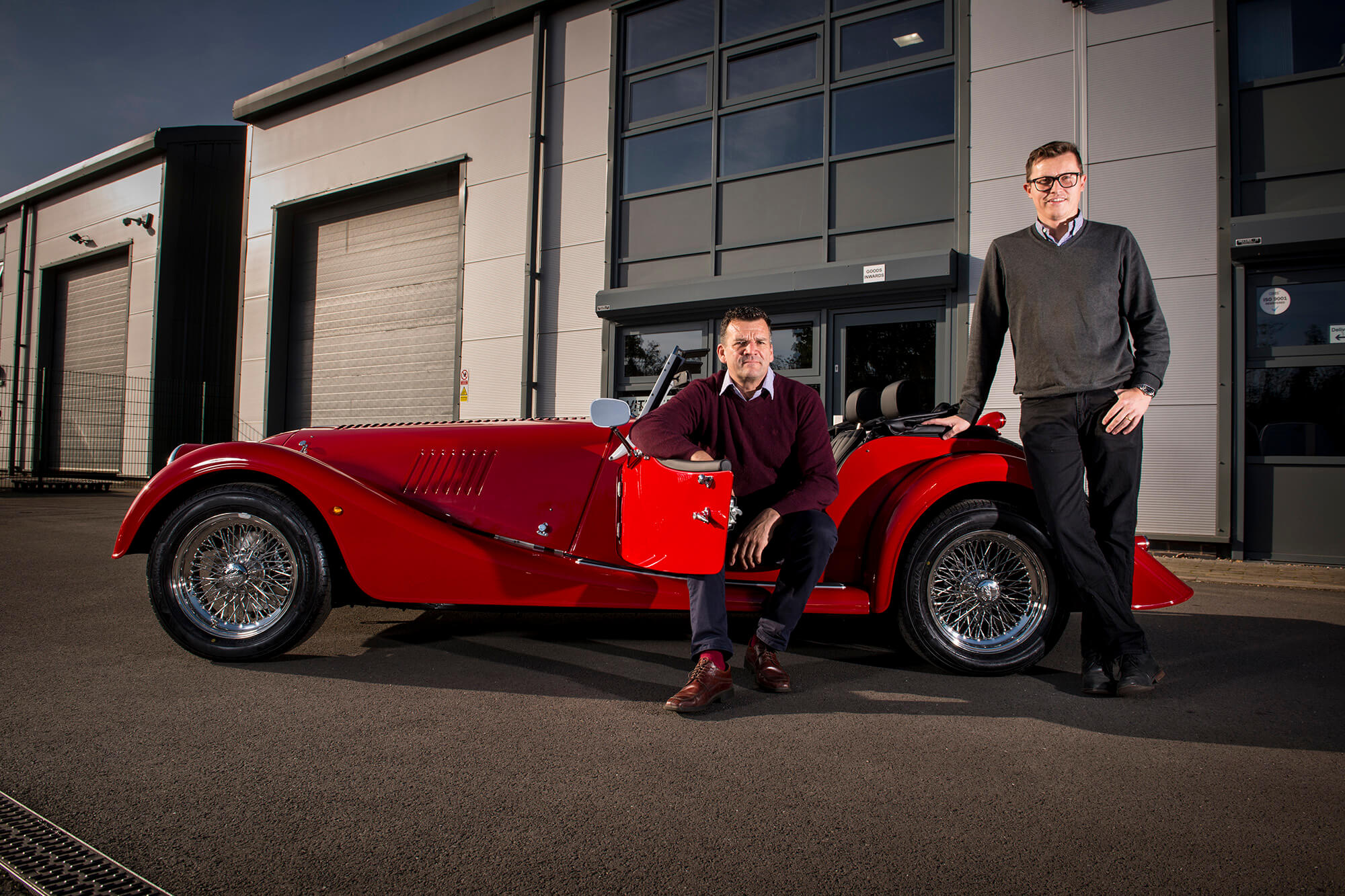 Two Vitesse staff stand next to and sit in a vintage open top red car