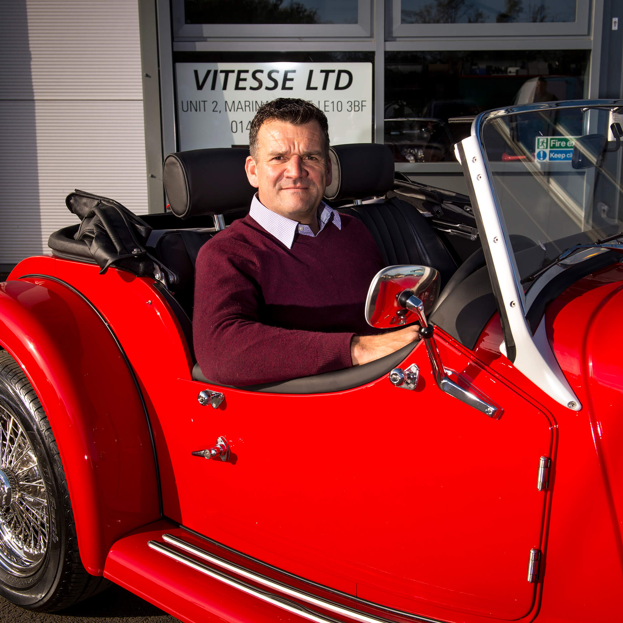 the Vitesse manager sits in a red vintage car