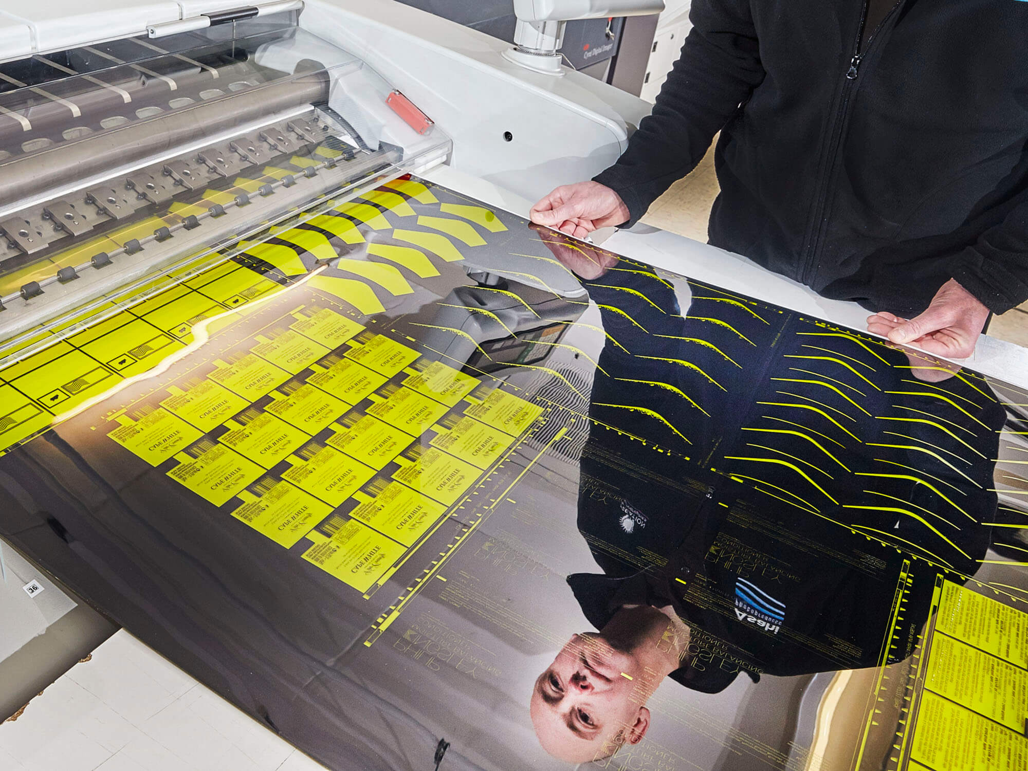 Member of Creation Reprographics staff is seen in his reflection on a shiny black printed surface with yellow graphics