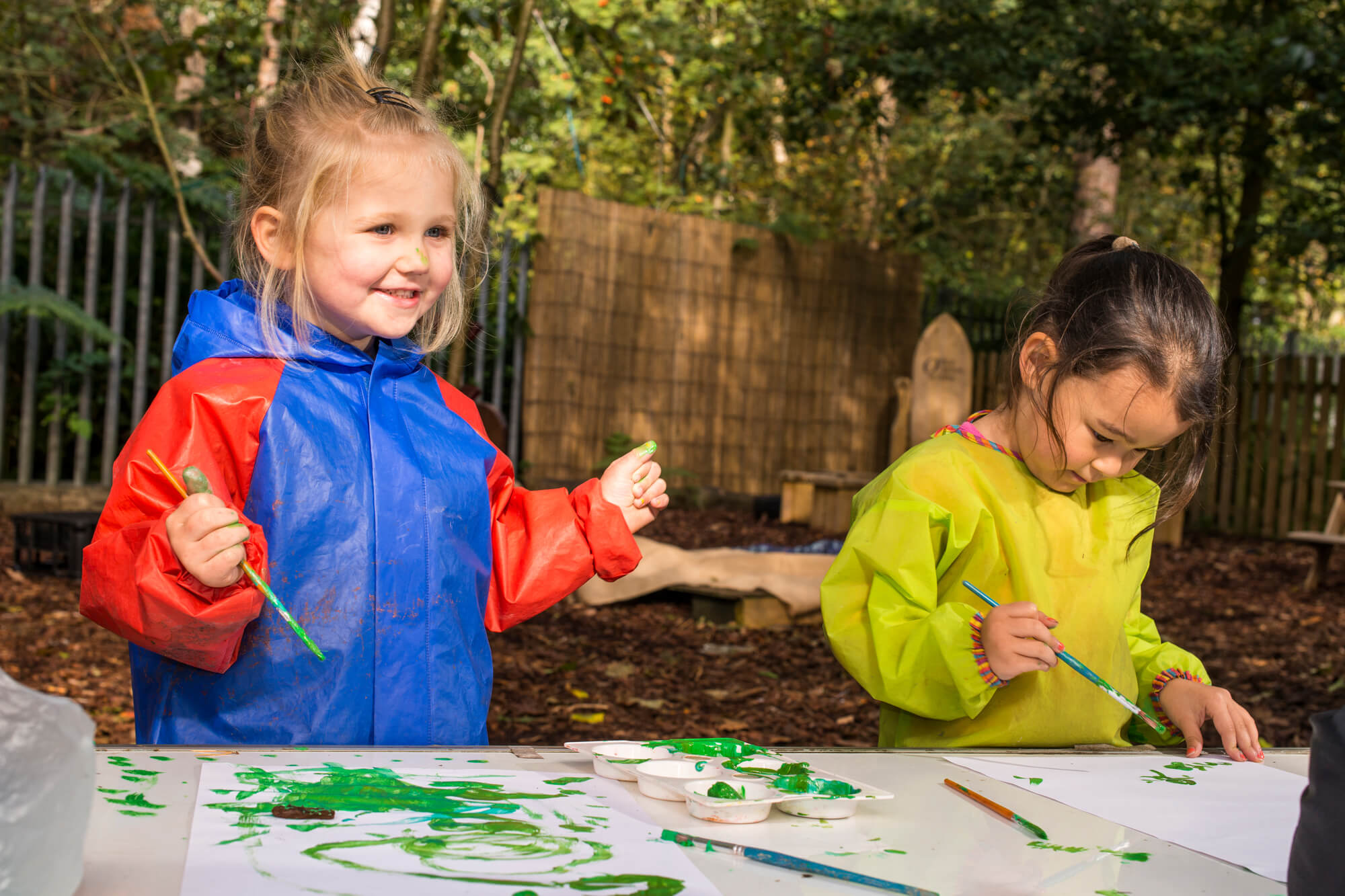 Pre school children enjoying painting outside