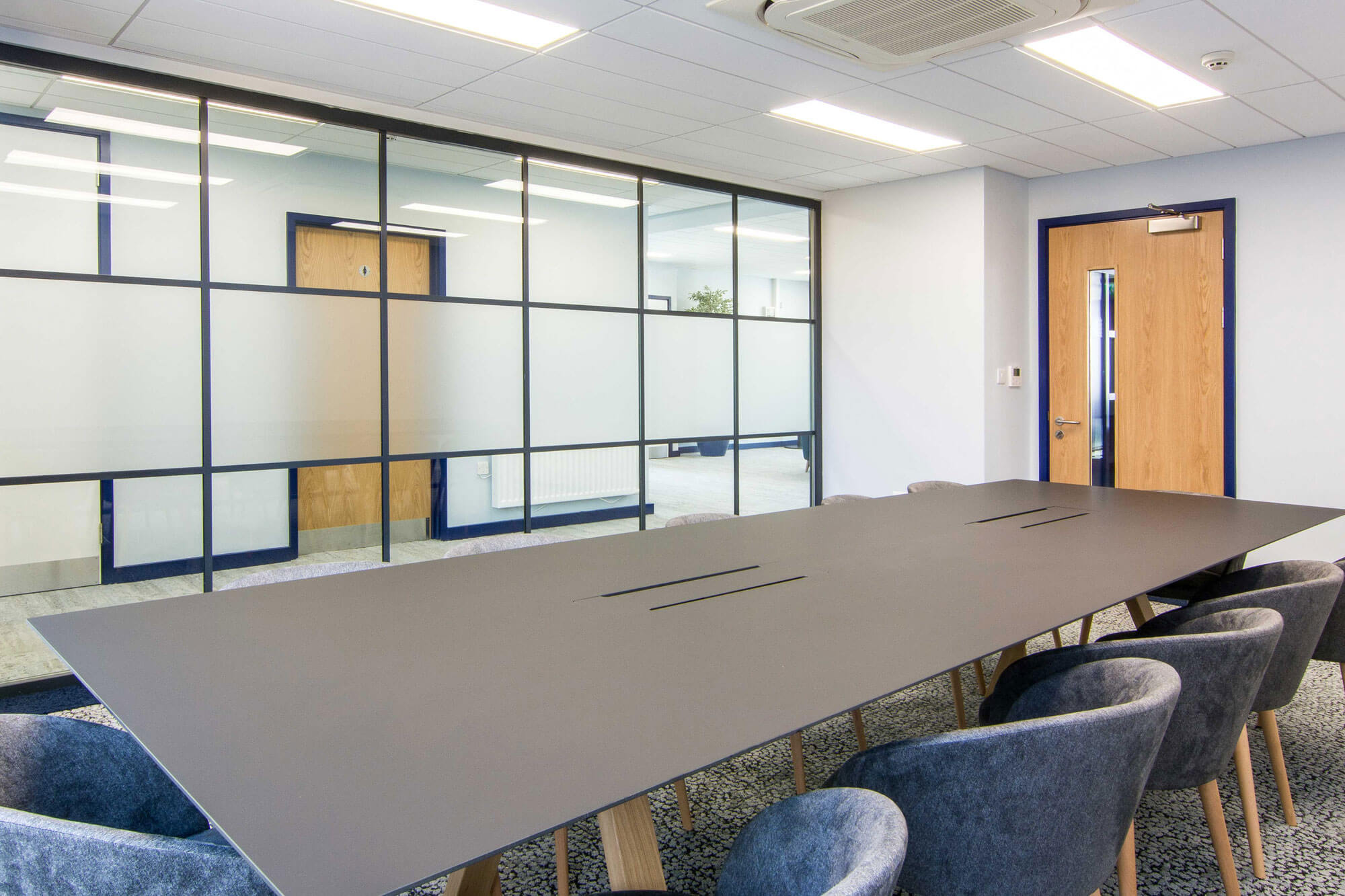 A large meeting room, in front a glass screen