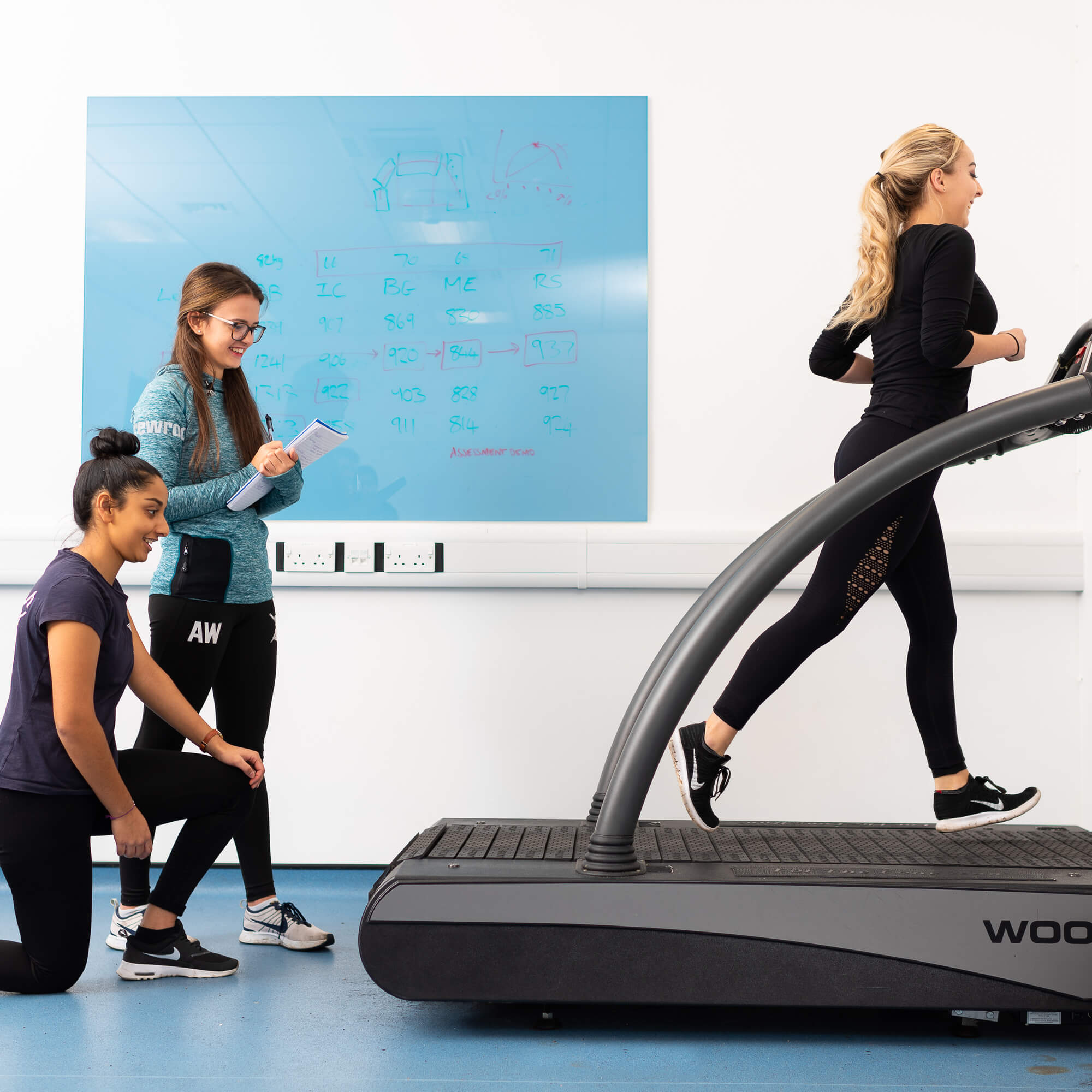 A blonde lady running on the treadmill and 2 people assessing her running