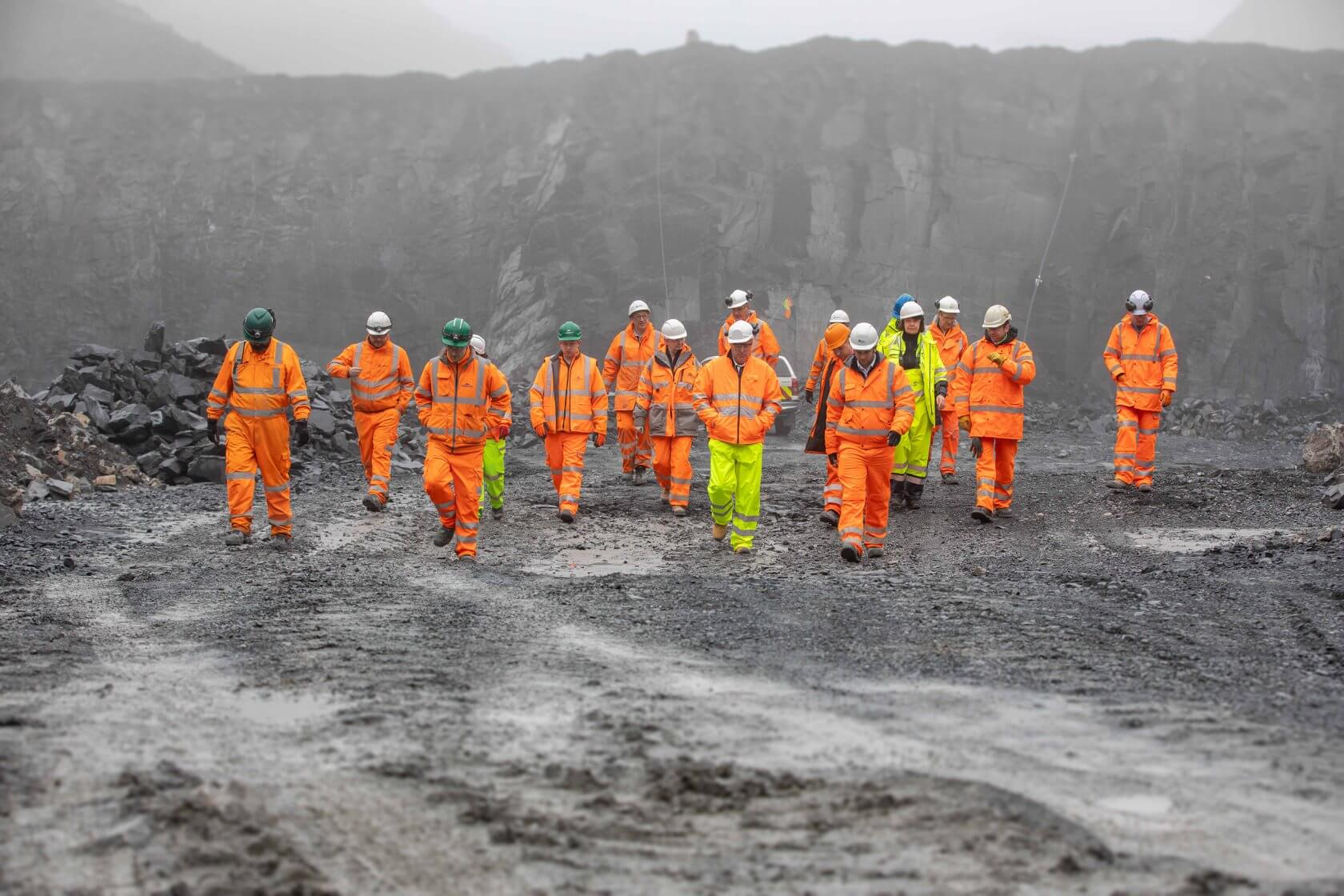 a group of people in a quarry in orange high vis