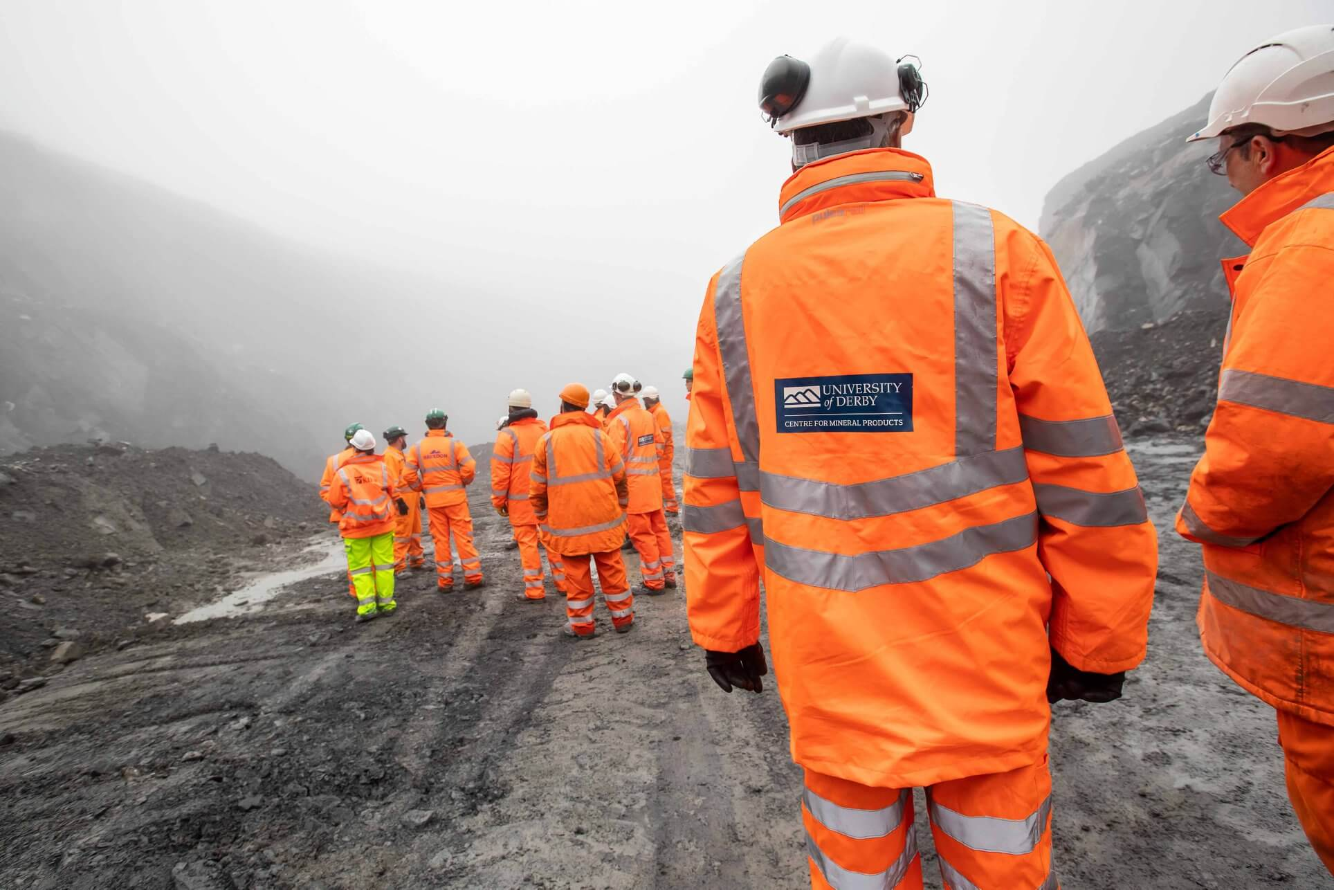 A group of students in orange high vis in a quarry