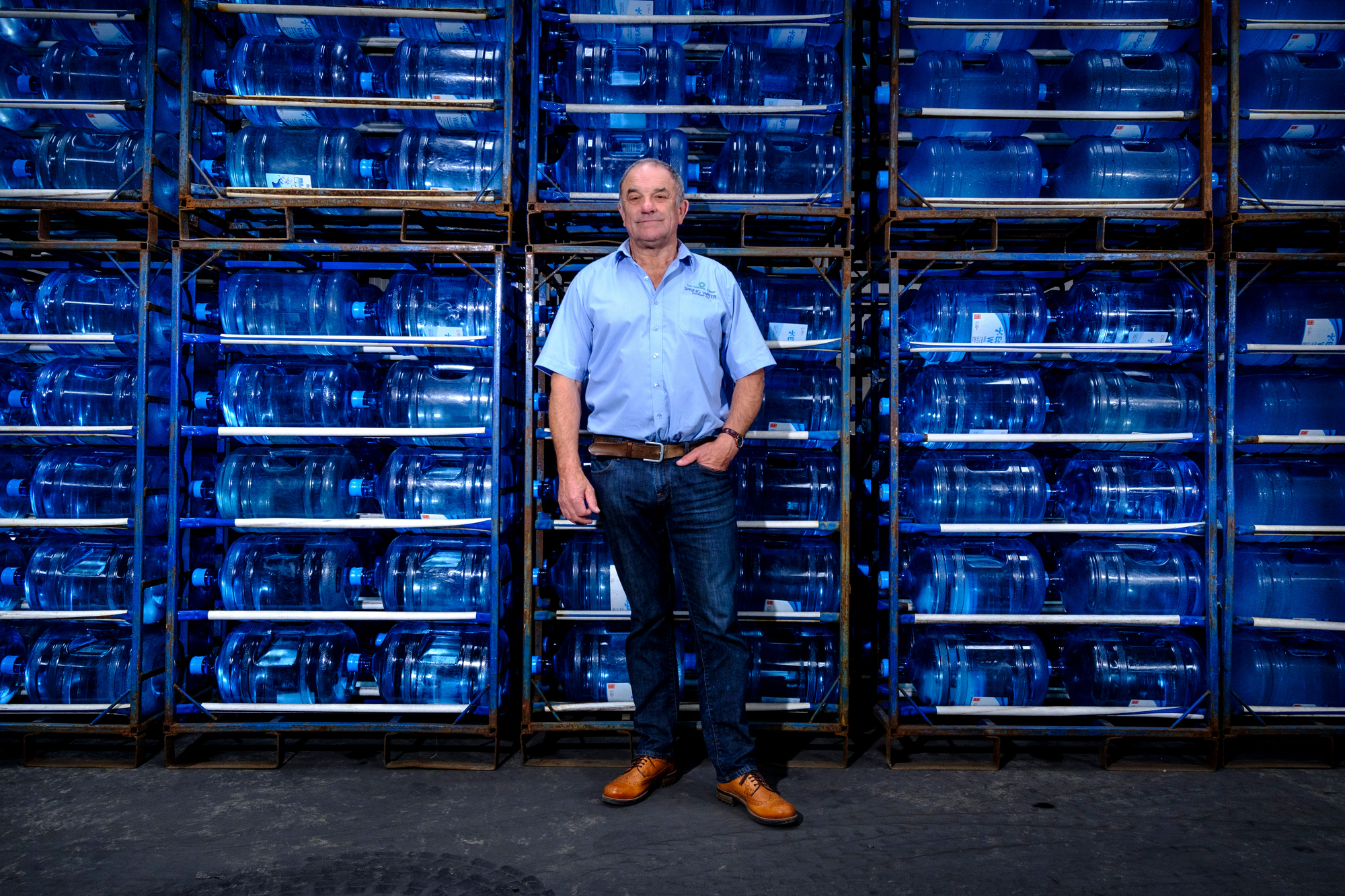 Man in corporate workwear stands in warehouse