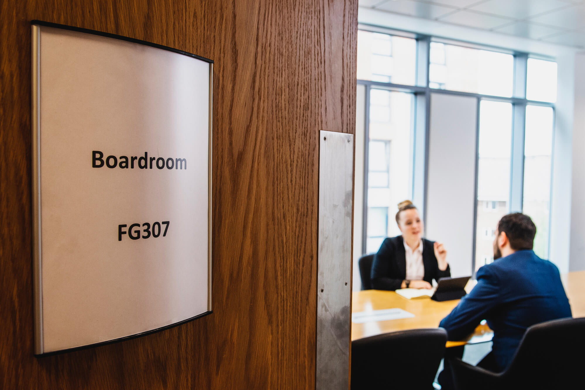 Boardroom door in foreground with two business people at table in background