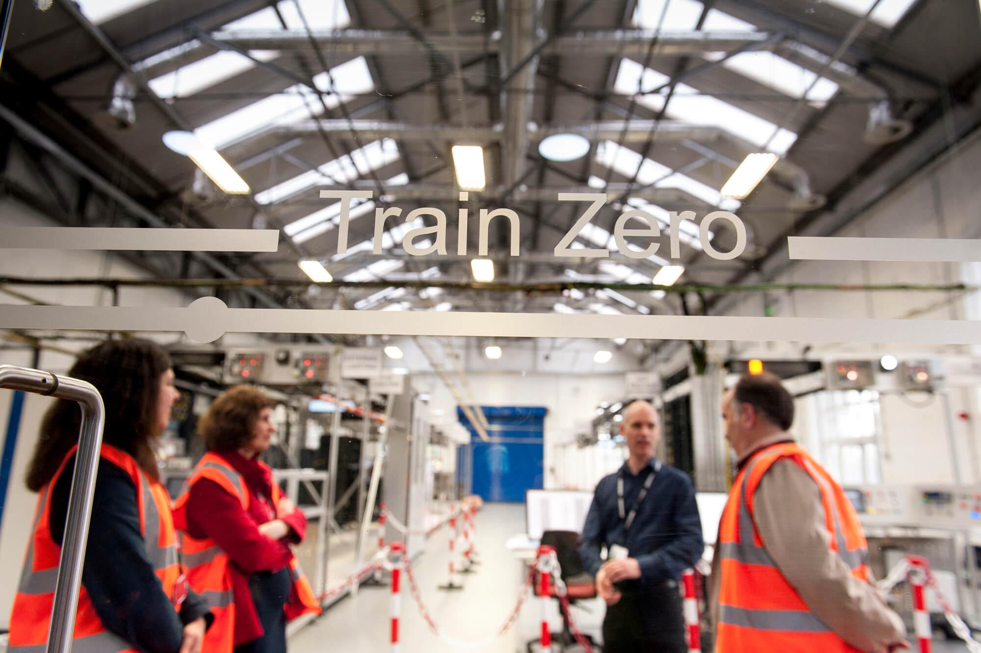 Four people talking inside Bombardier factory