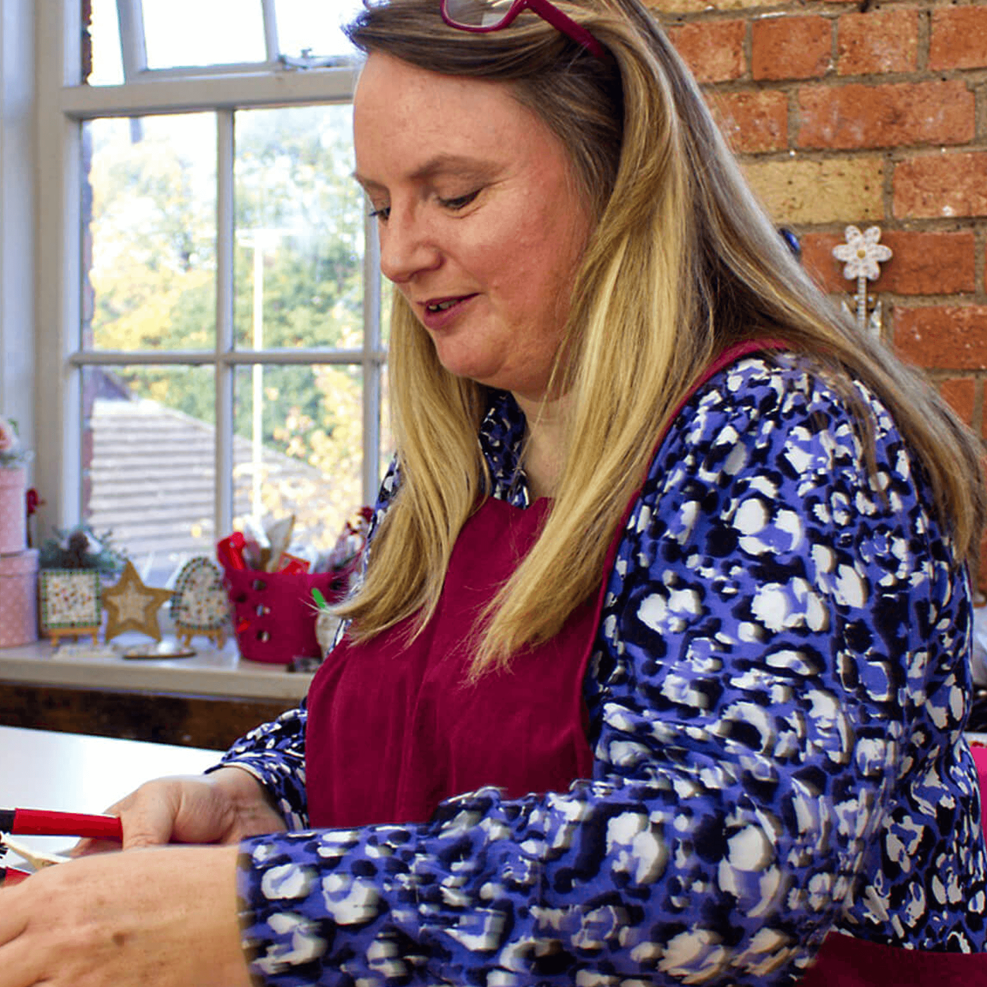 A blonde lady wearing a burgundy apron, over a blue floral shirt