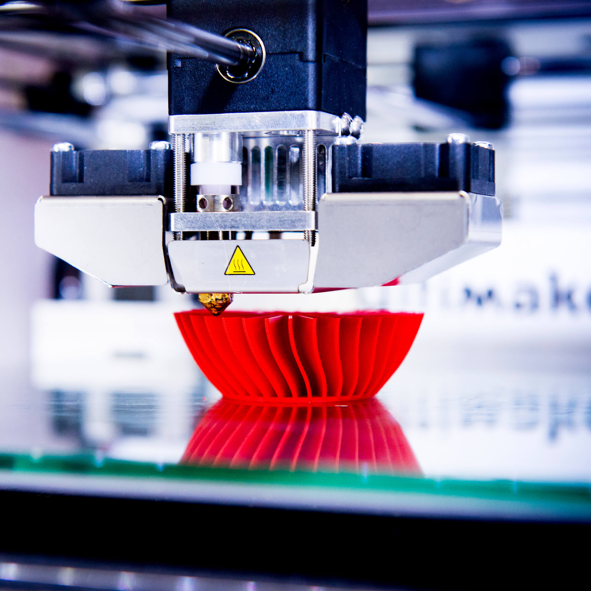 3D printer creating a red 3D product