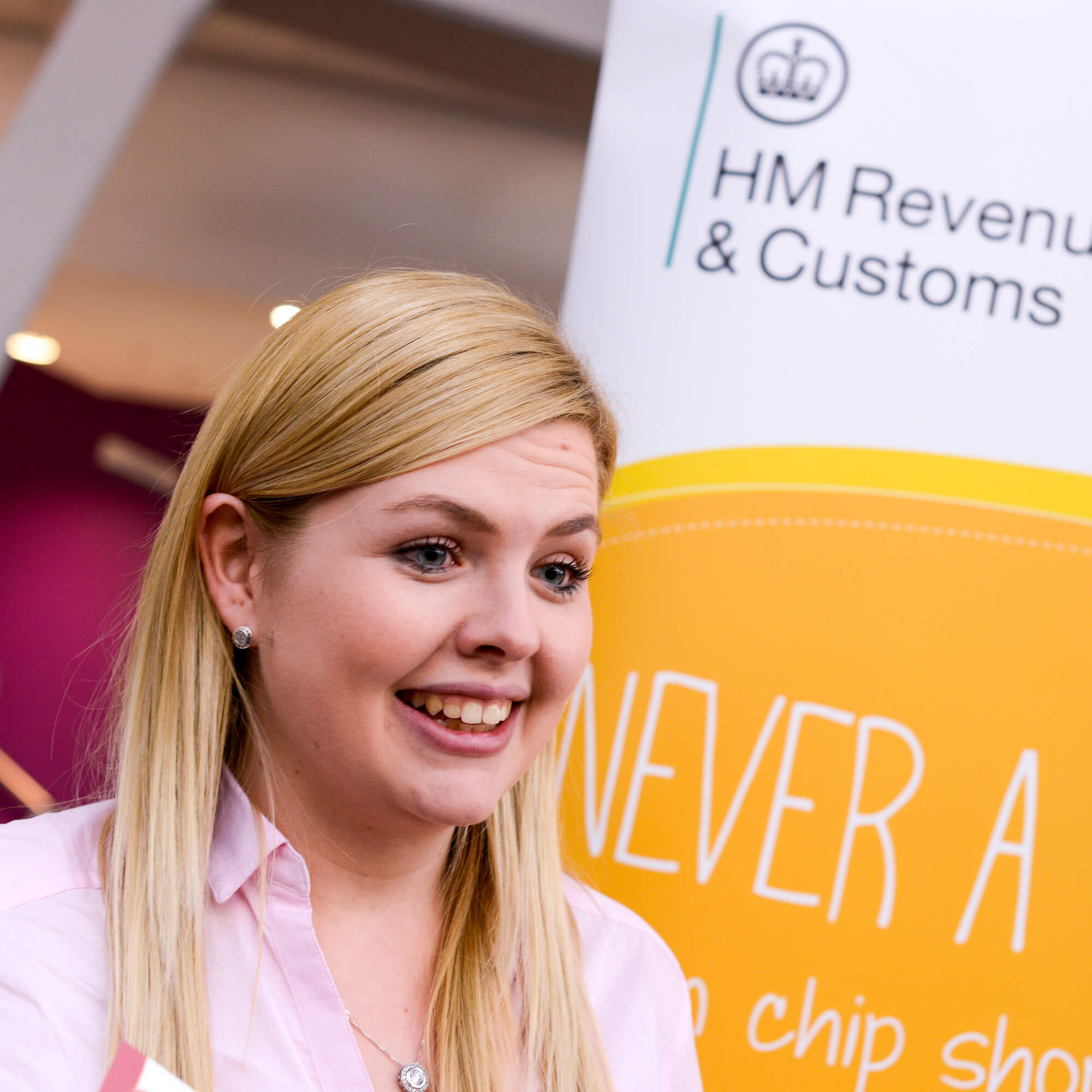 Employee talking in front of business stand at event