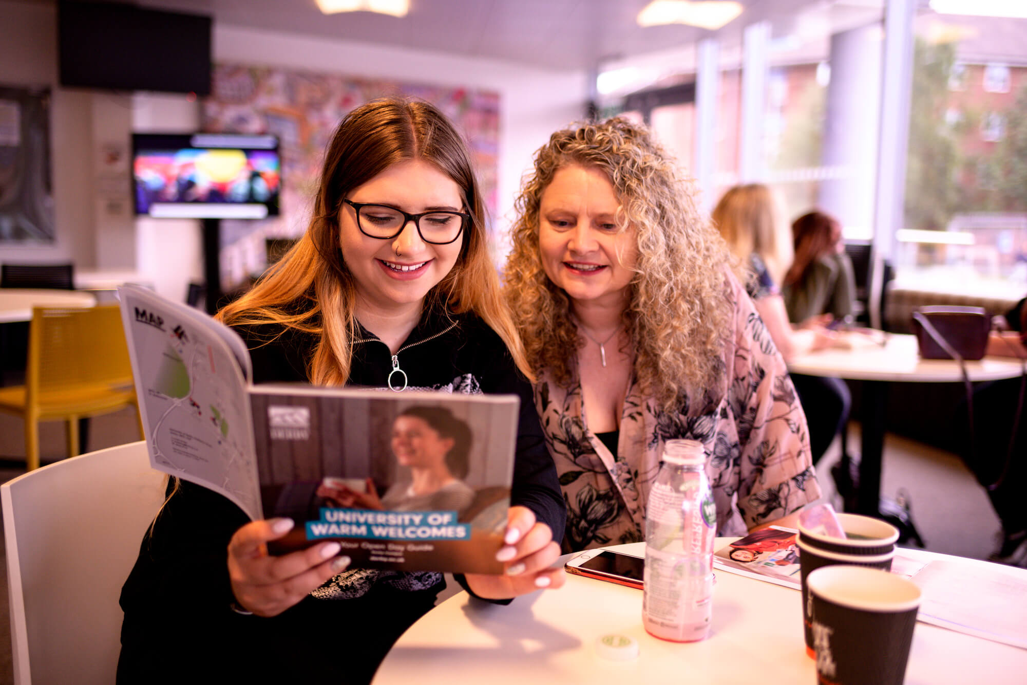 Two ladies reading an open day guide, smiling