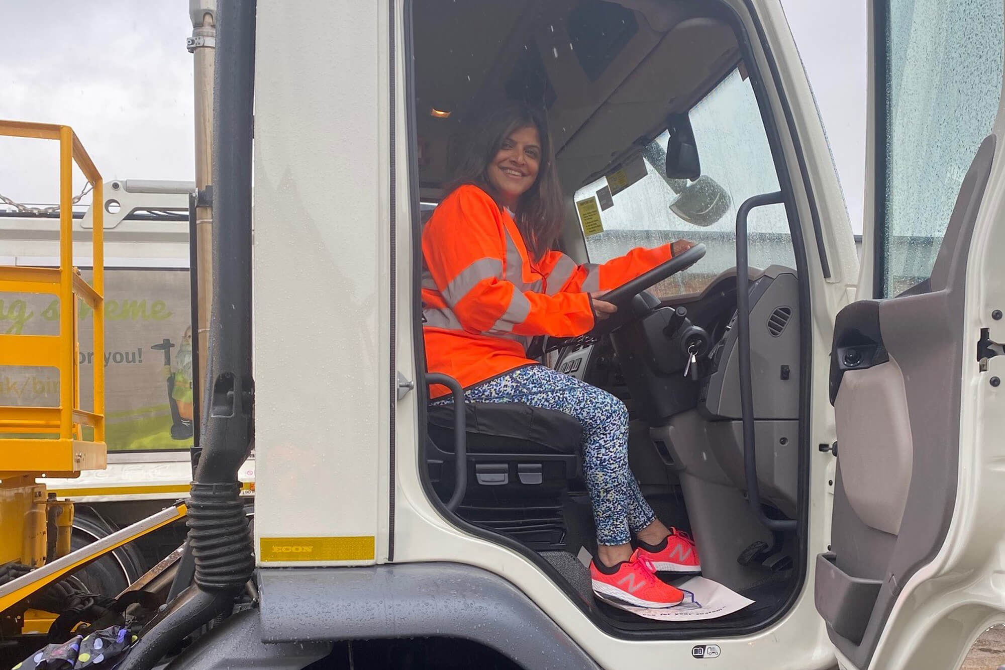 A lady in a orange high vis vest, smiling in the cab of a lorry.
