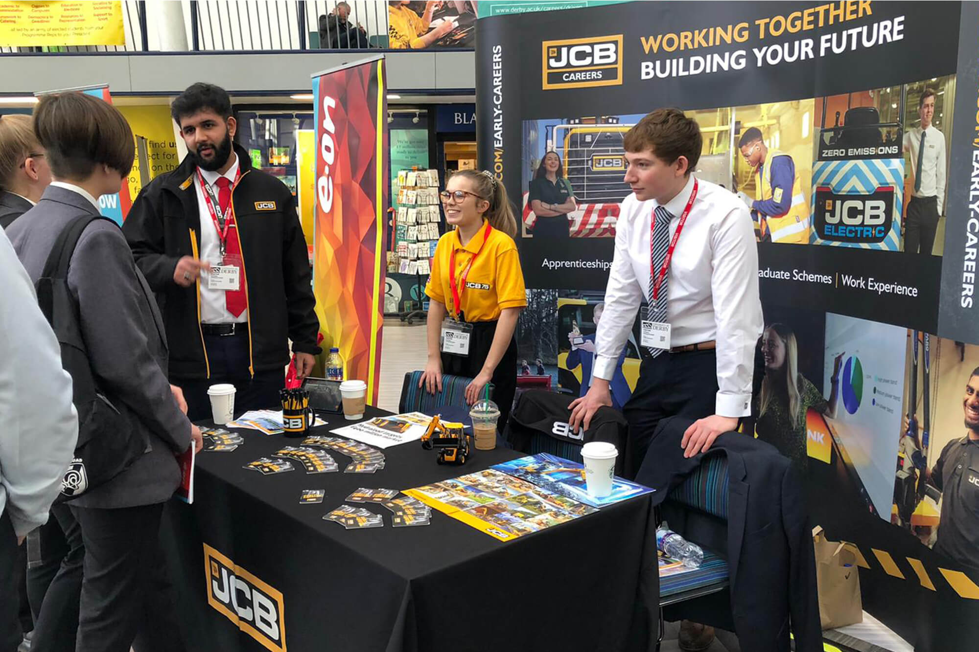 Molly standing at a table covered in a black table cloth and in front of a JCB screen, talking to people in a crowd.