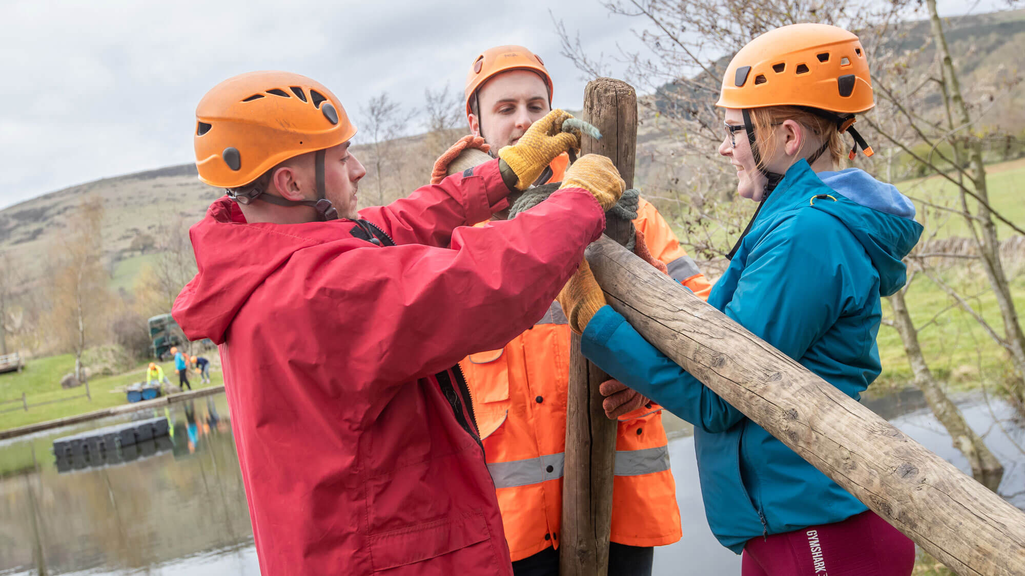3 students in high vis jackets, tying a rope to a piece of wood