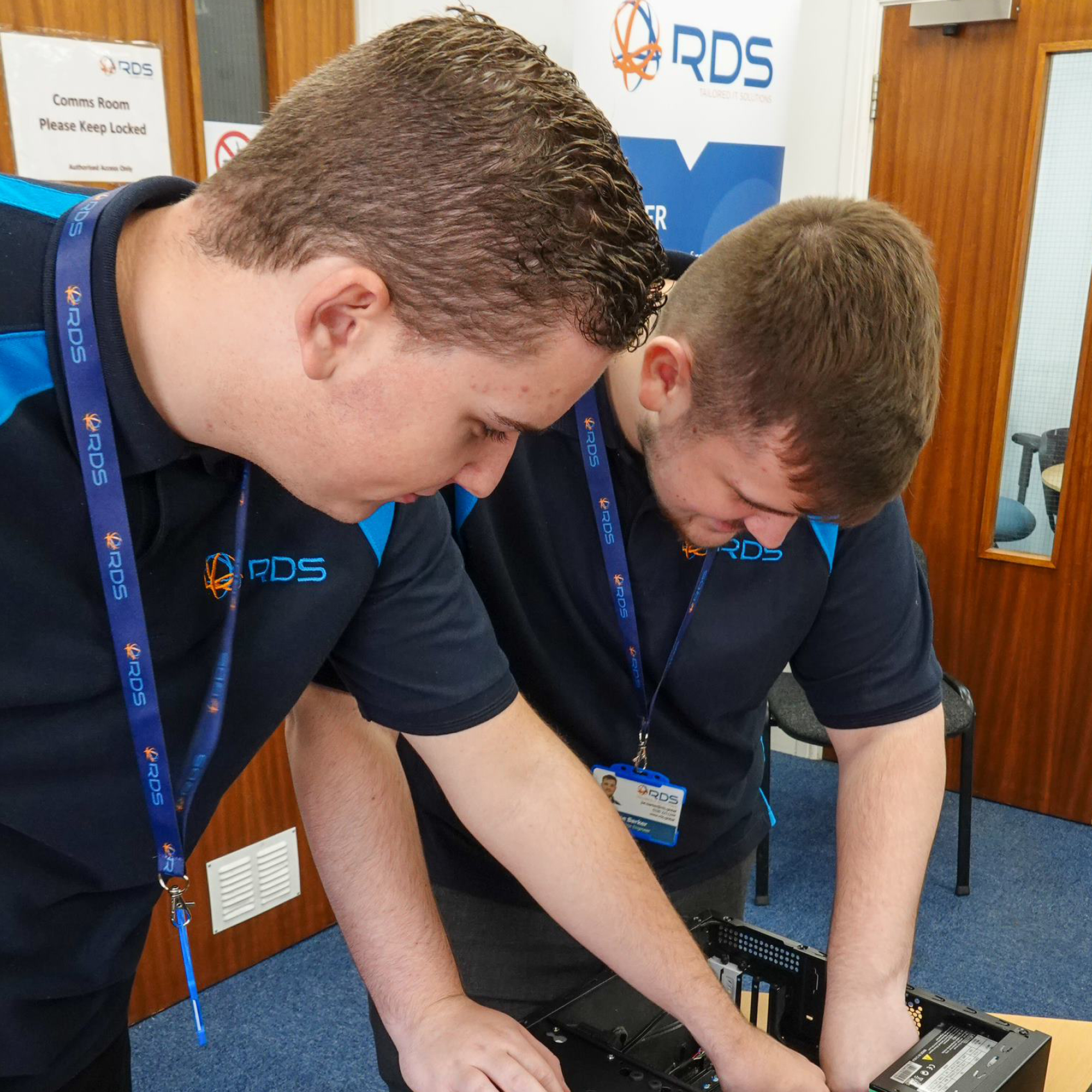 Two apprentices looking at piece of equipment in blue polo shirts