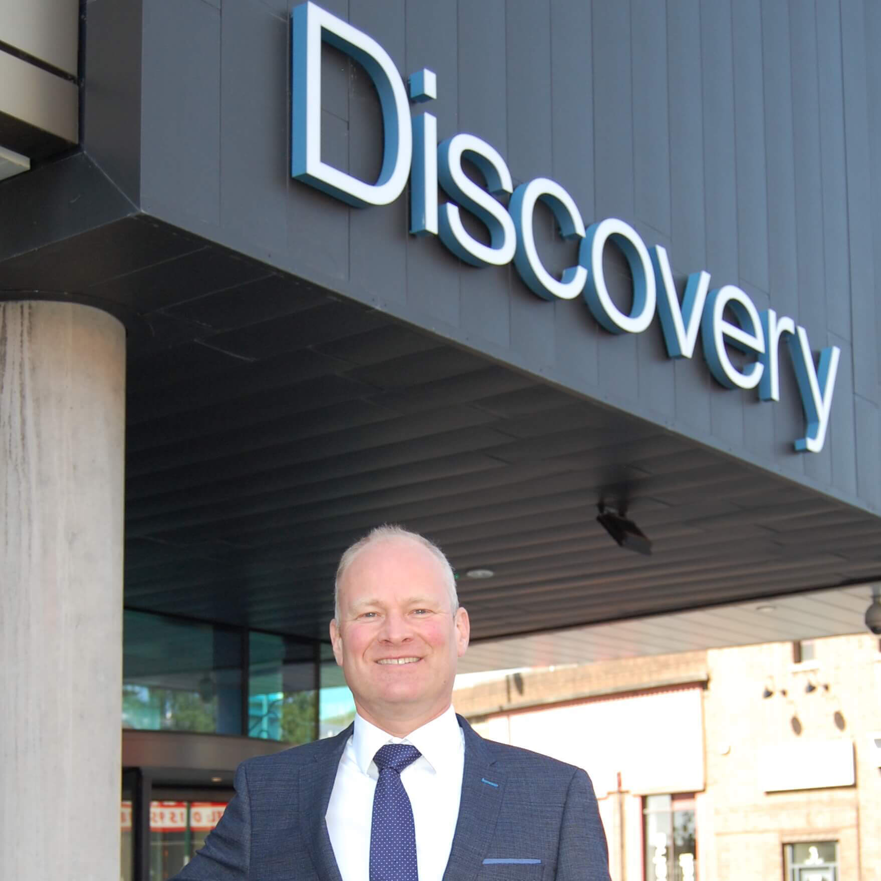 Man smiling in front of a discovery sign
