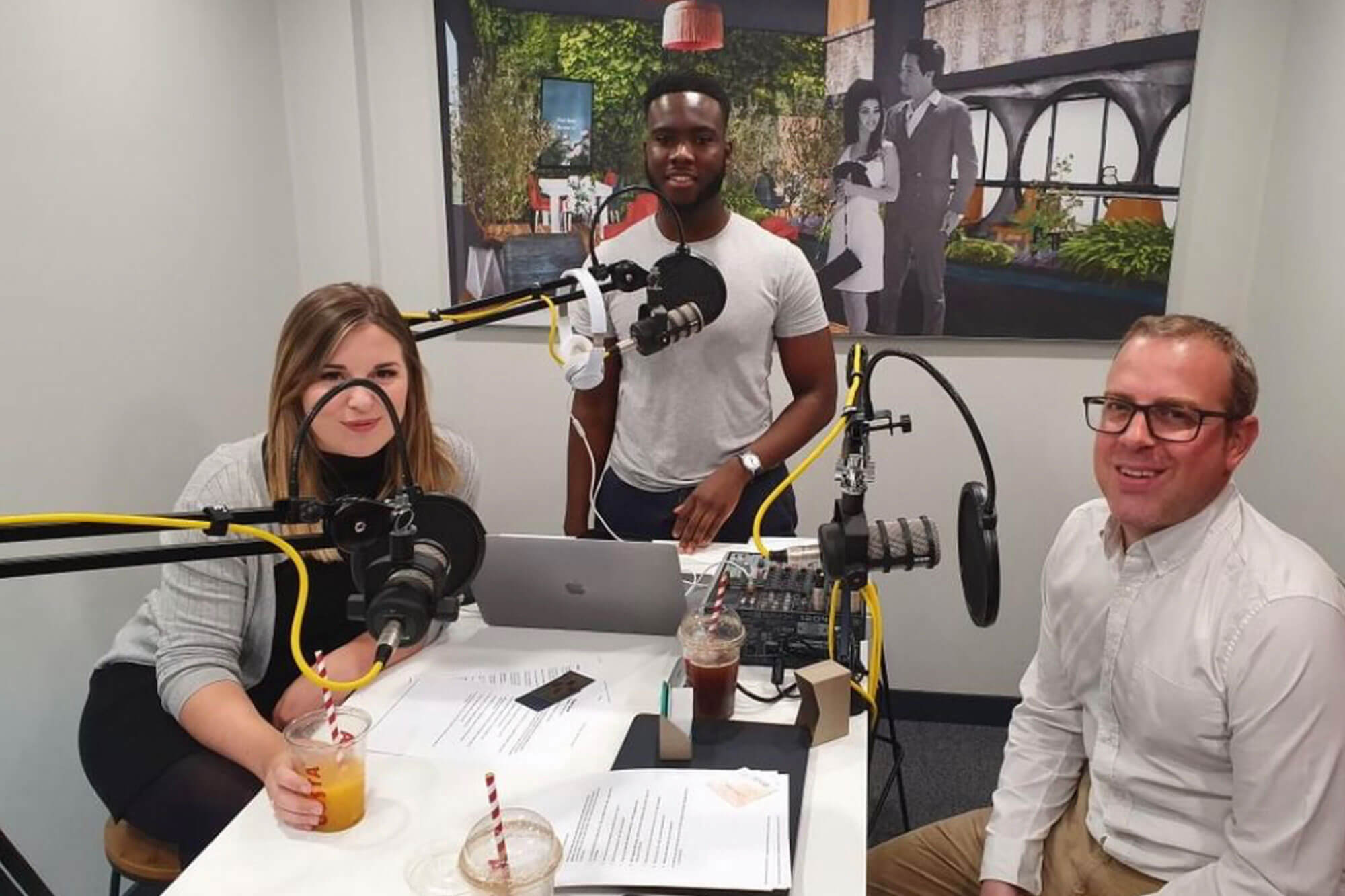 3 people, 2 men and a girl, looking at the camera around podcast equipment.