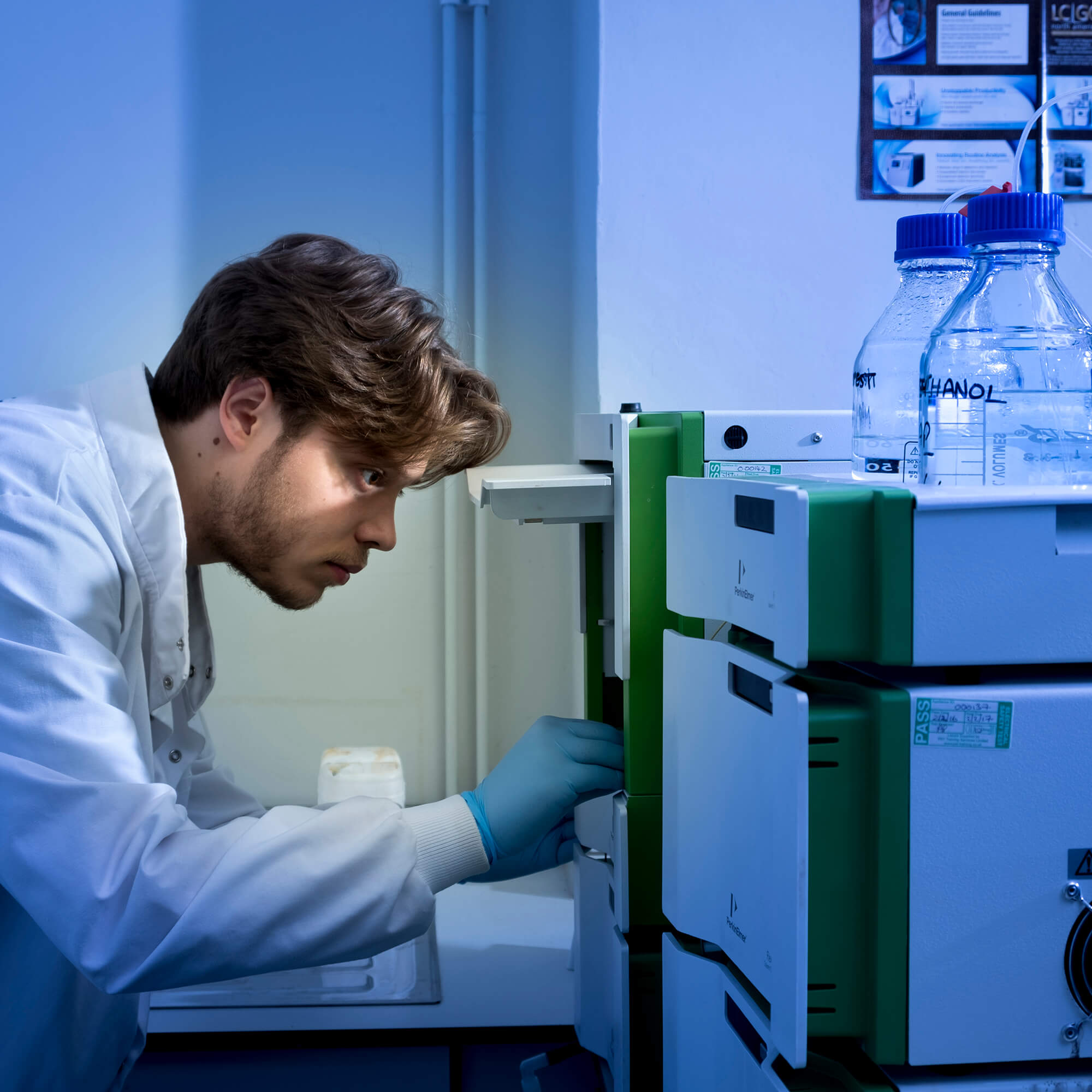 A man wearing a white coat looking into a microscope