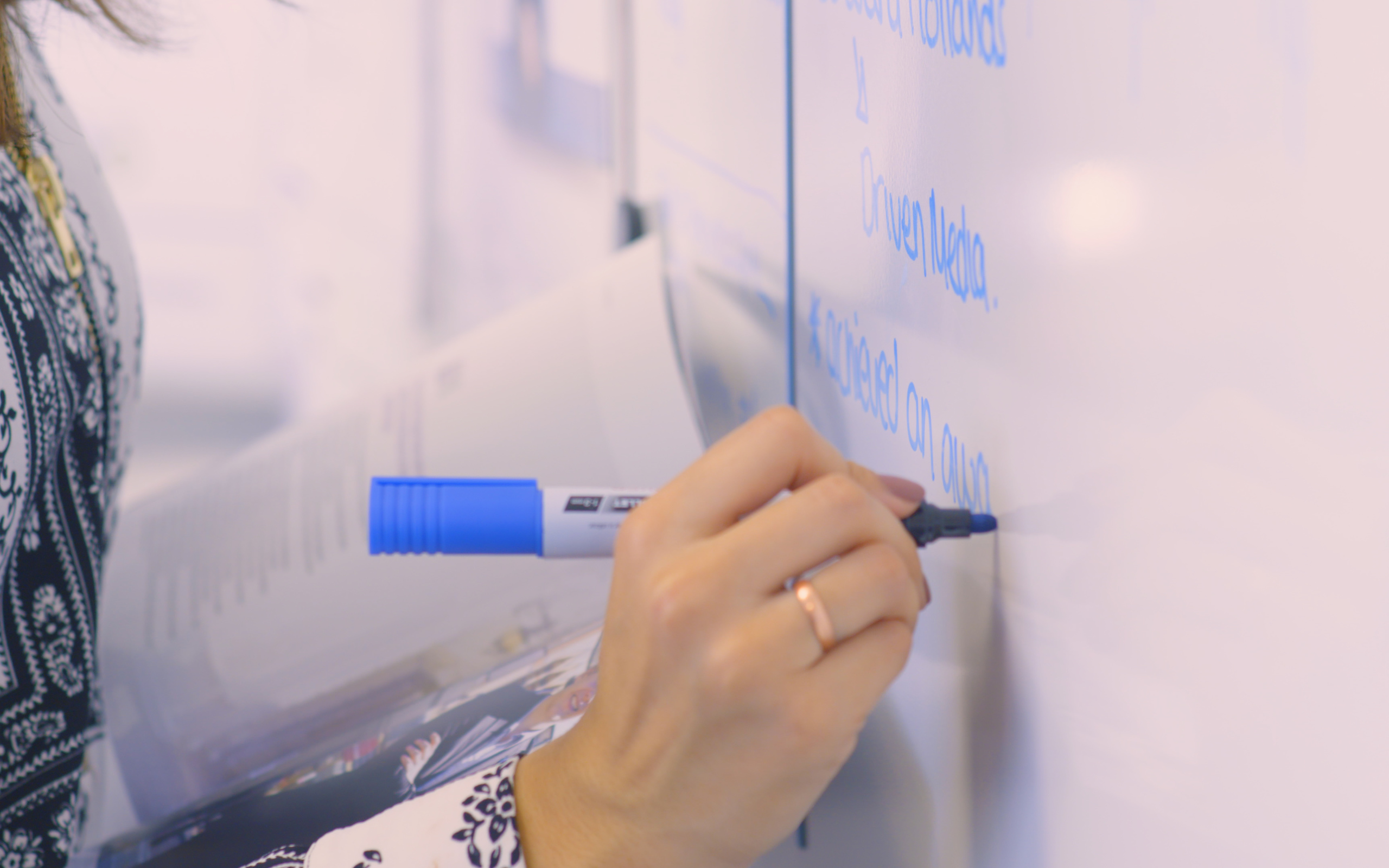 Close up of hand writing on a whiteboard
