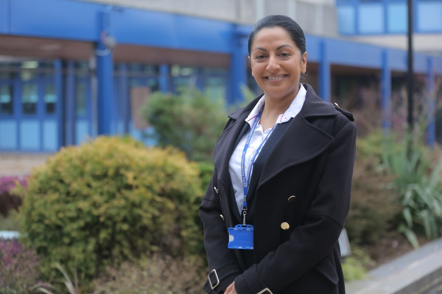 PC Rai-Mottram standing in front of a blue building and smiling at the camera