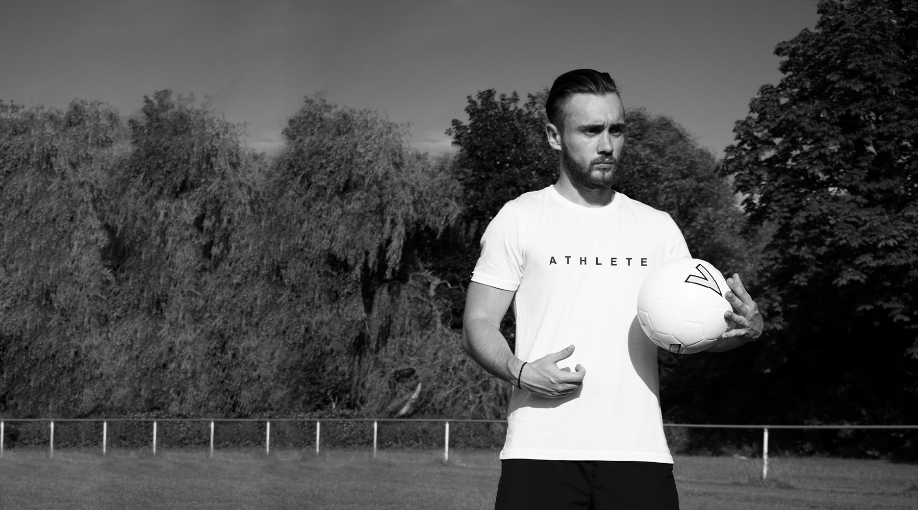 Black and white photo of a man holding a football on a football pitch