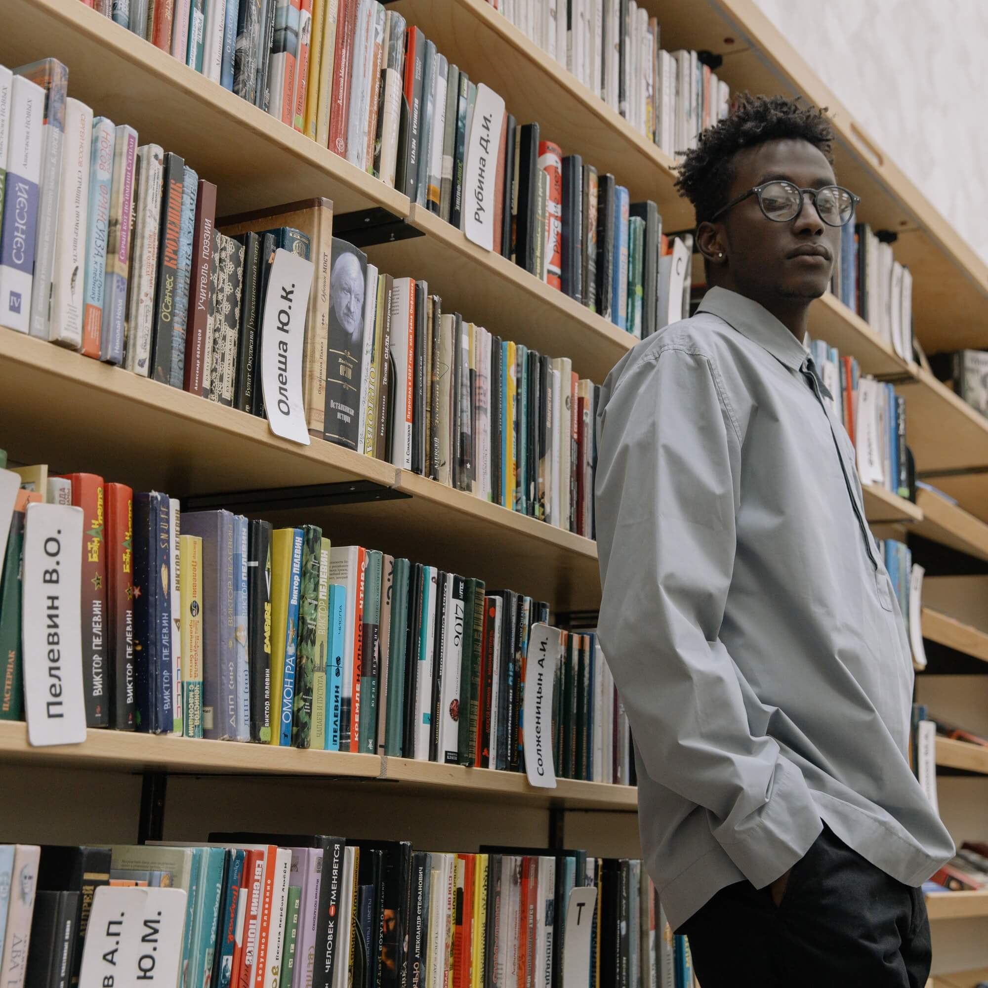 Person standing next to a bookcase.