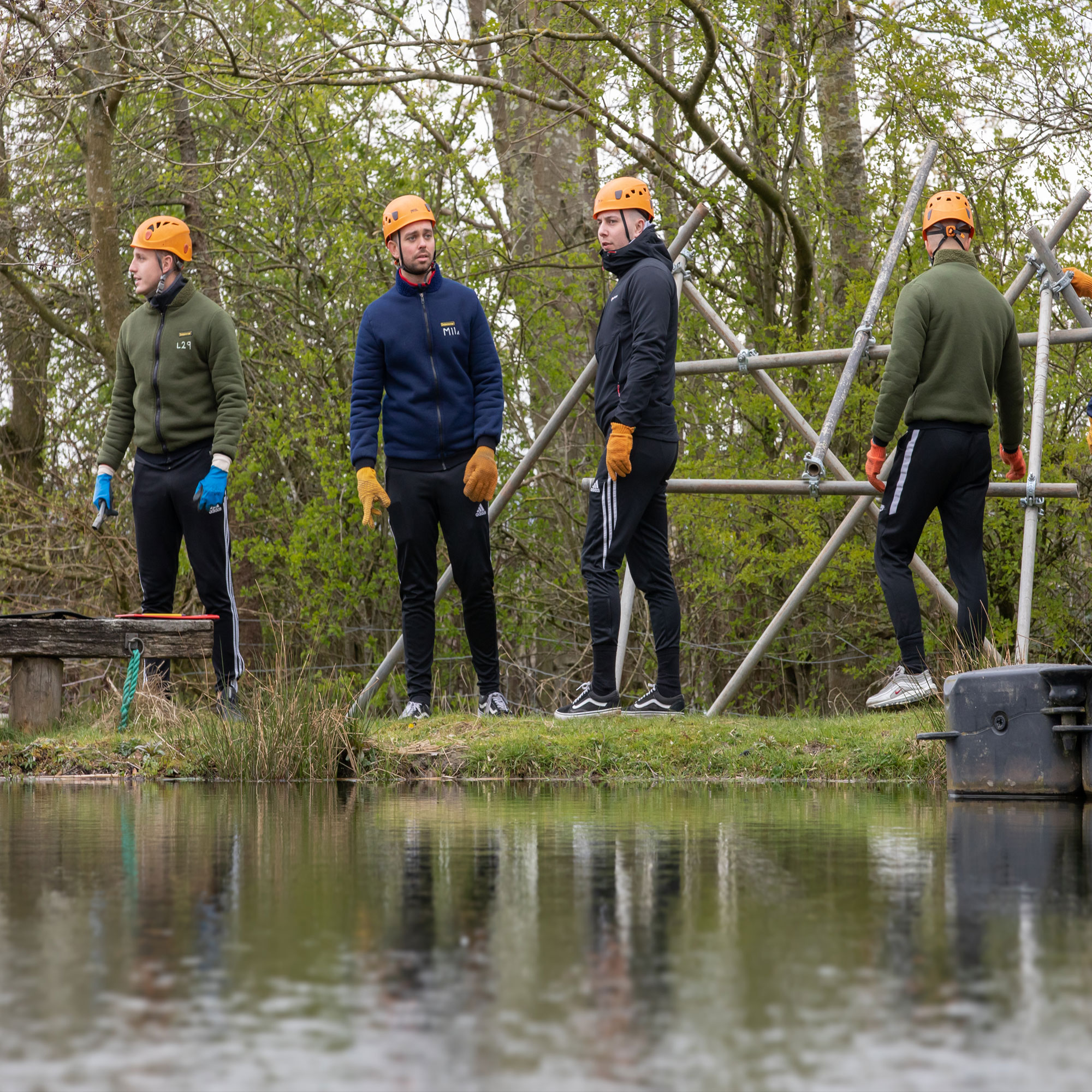 A group of men standing on the side of a lake in hard hats