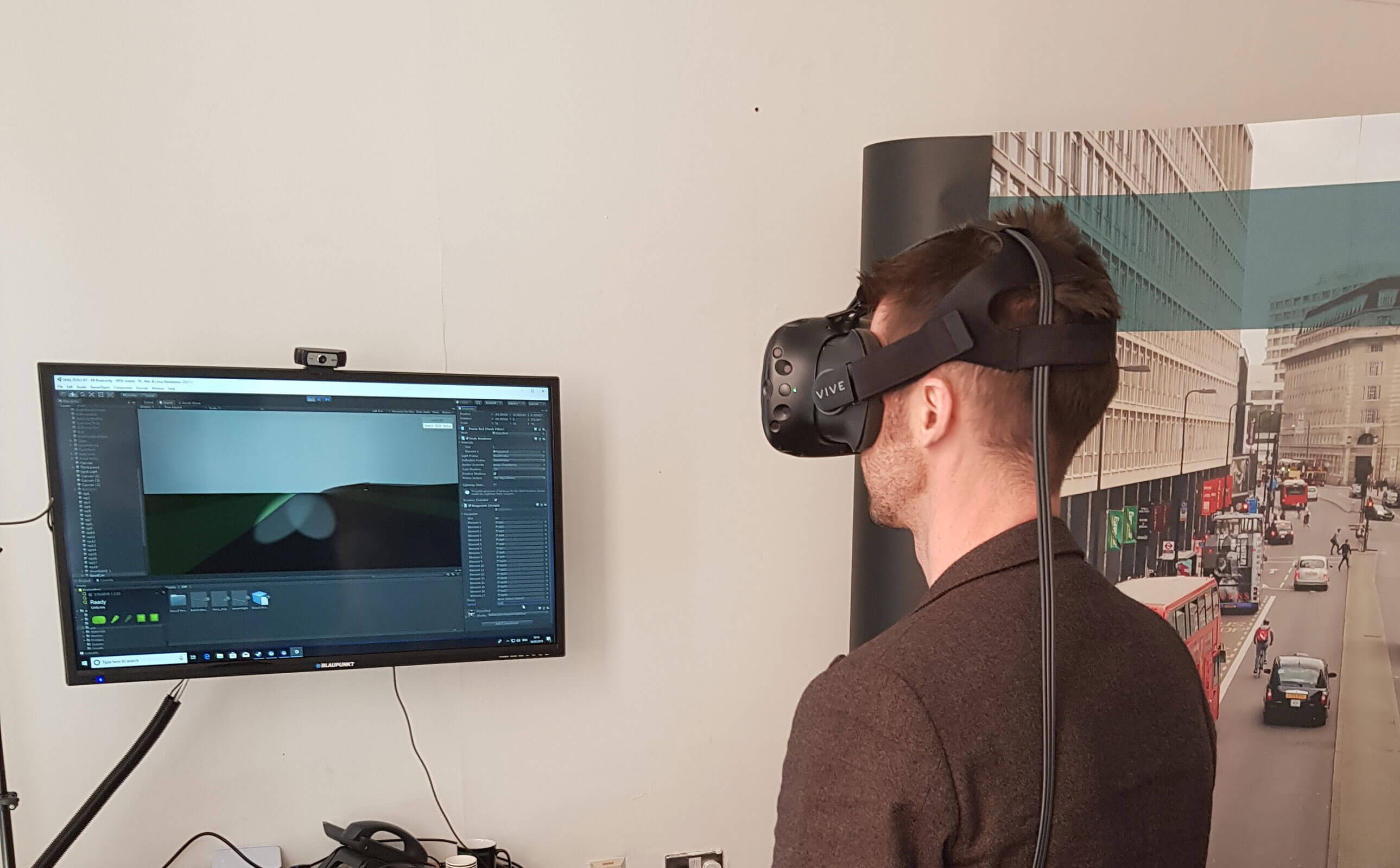 A man using the virtual reality headset and looking at a computer