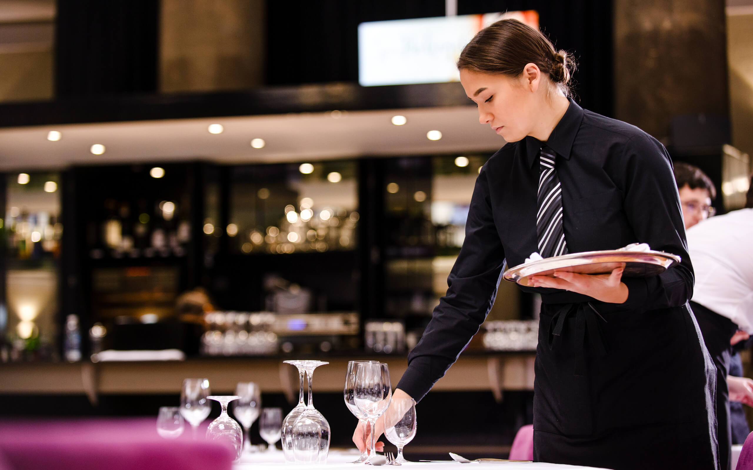 Young female laying table in restaurant