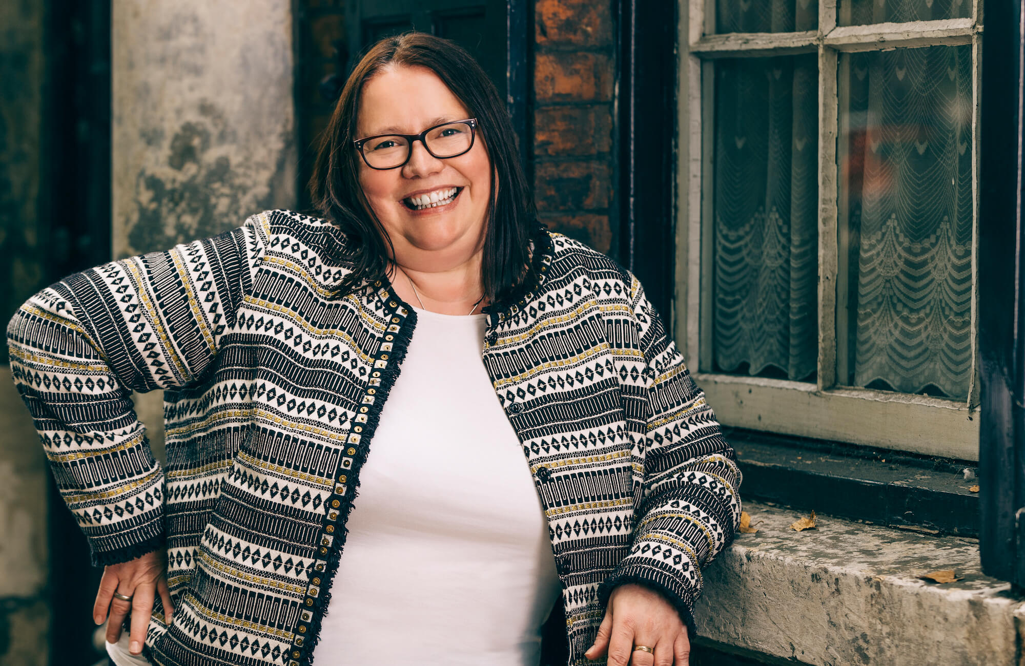 A lady wearing glasses smiling